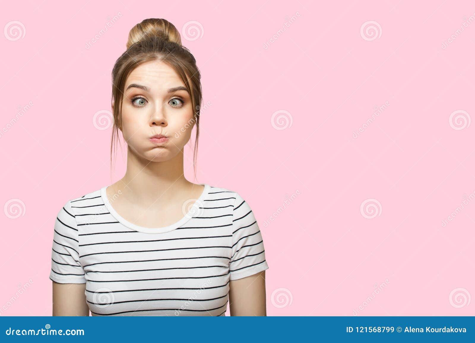 Mejillas que soplan de la mujer divertida Fondo rosado
