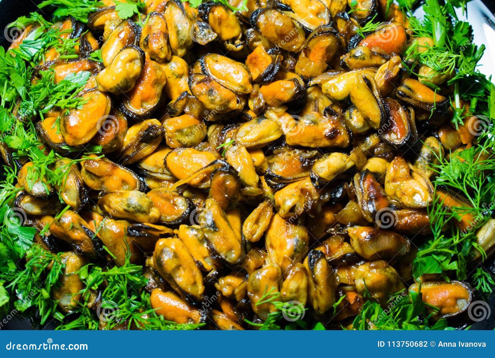 Mejillones apetitosos fritos café en un plato, adornado con verdor