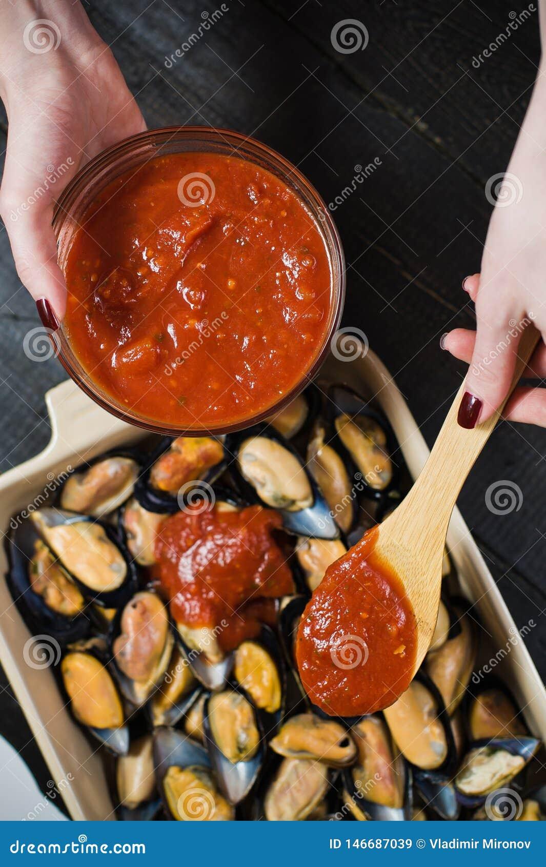 Mejillones crudos con la pasta de tomate en el fondo negro, cocinando