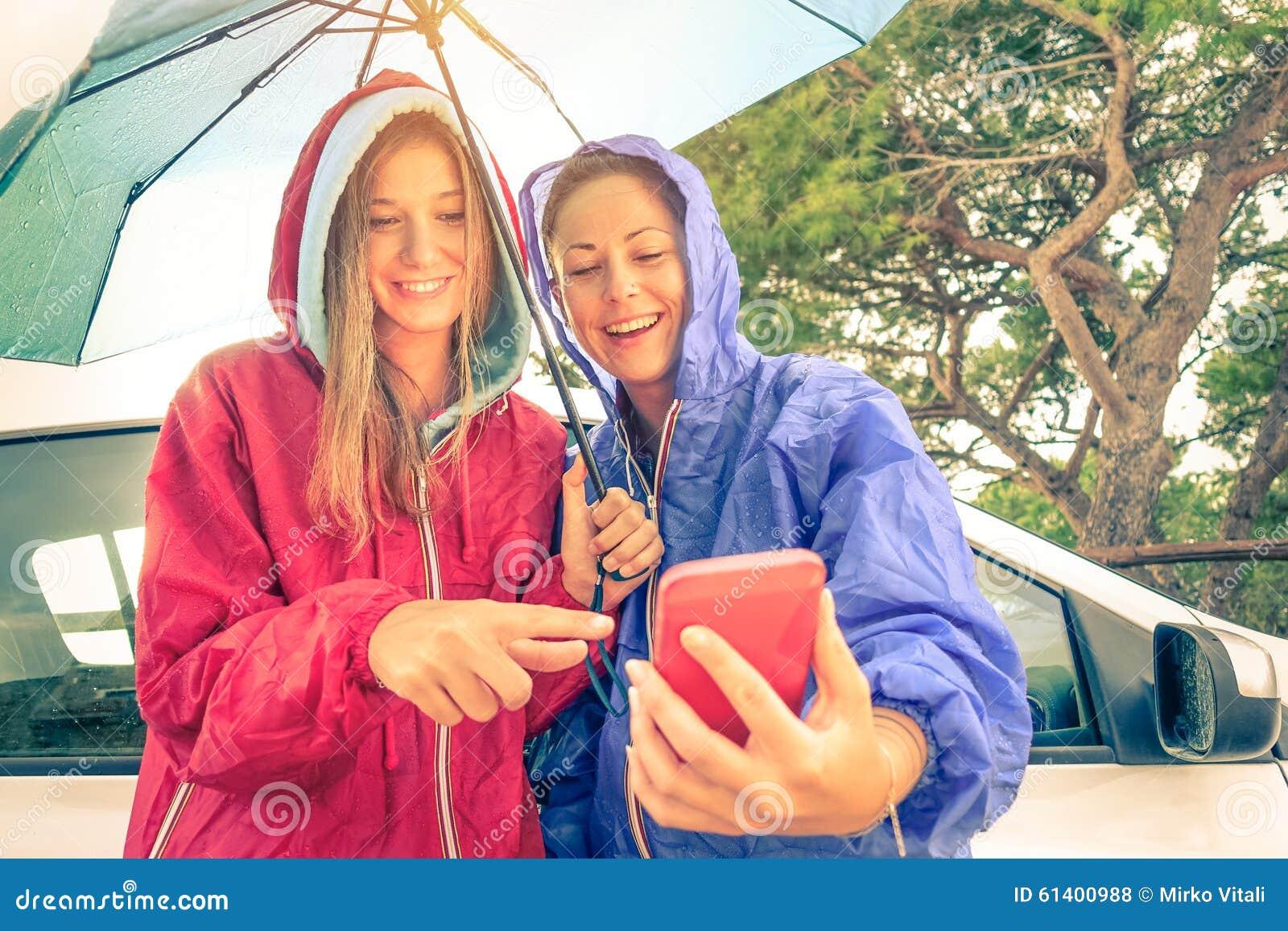 Mejores amigos de las mujeres que gozan con smartphone con el sol que sale