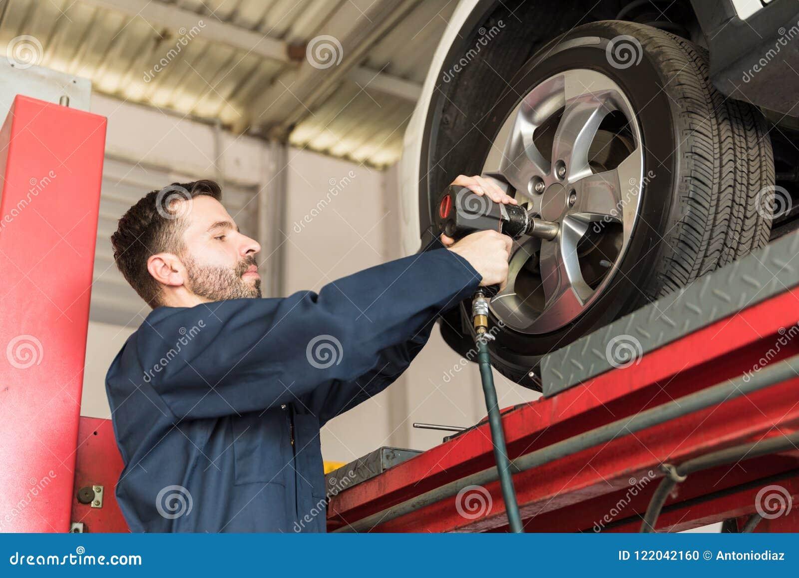 Mekaniker Servicing Car Tire med inverkanvapnet i garage