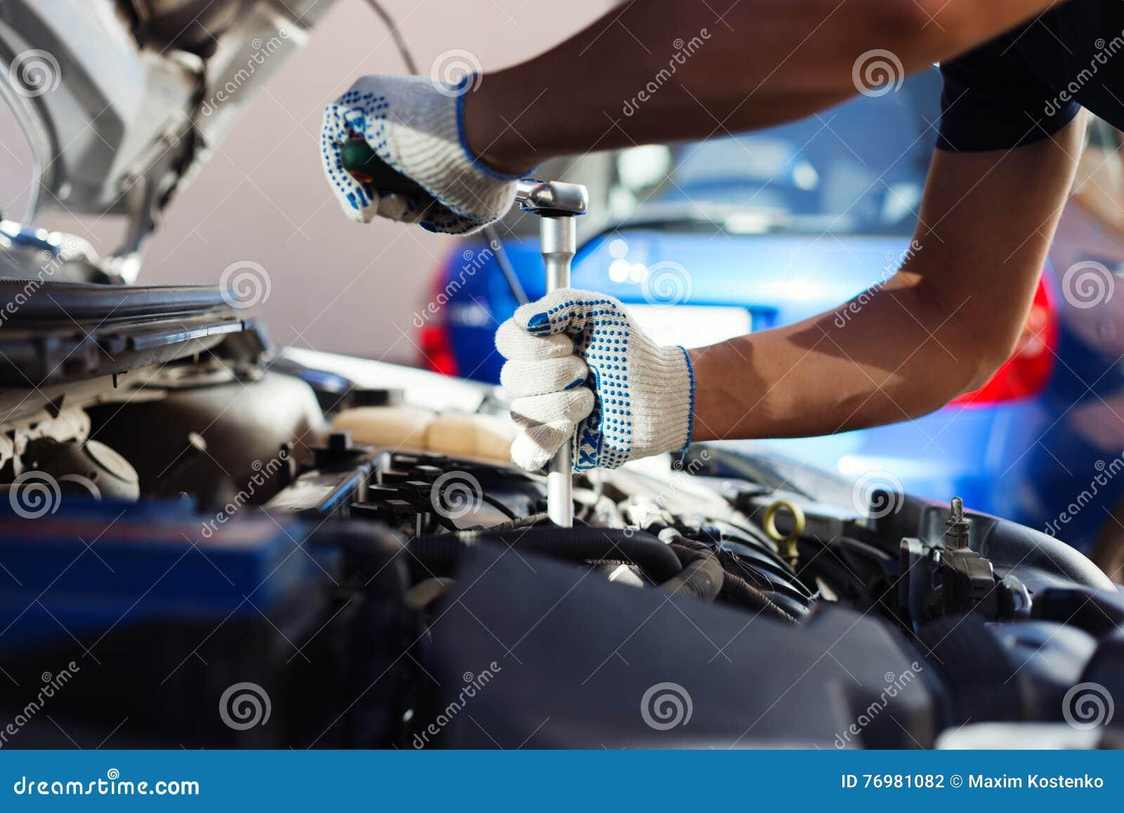 Mekaniker som arbetar i garage för auto reparation Bilunderhåll
