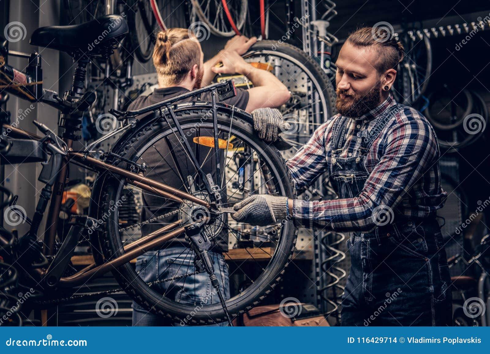 Mekaniker som gör handboken för service för cykelhjul i ett seminarium