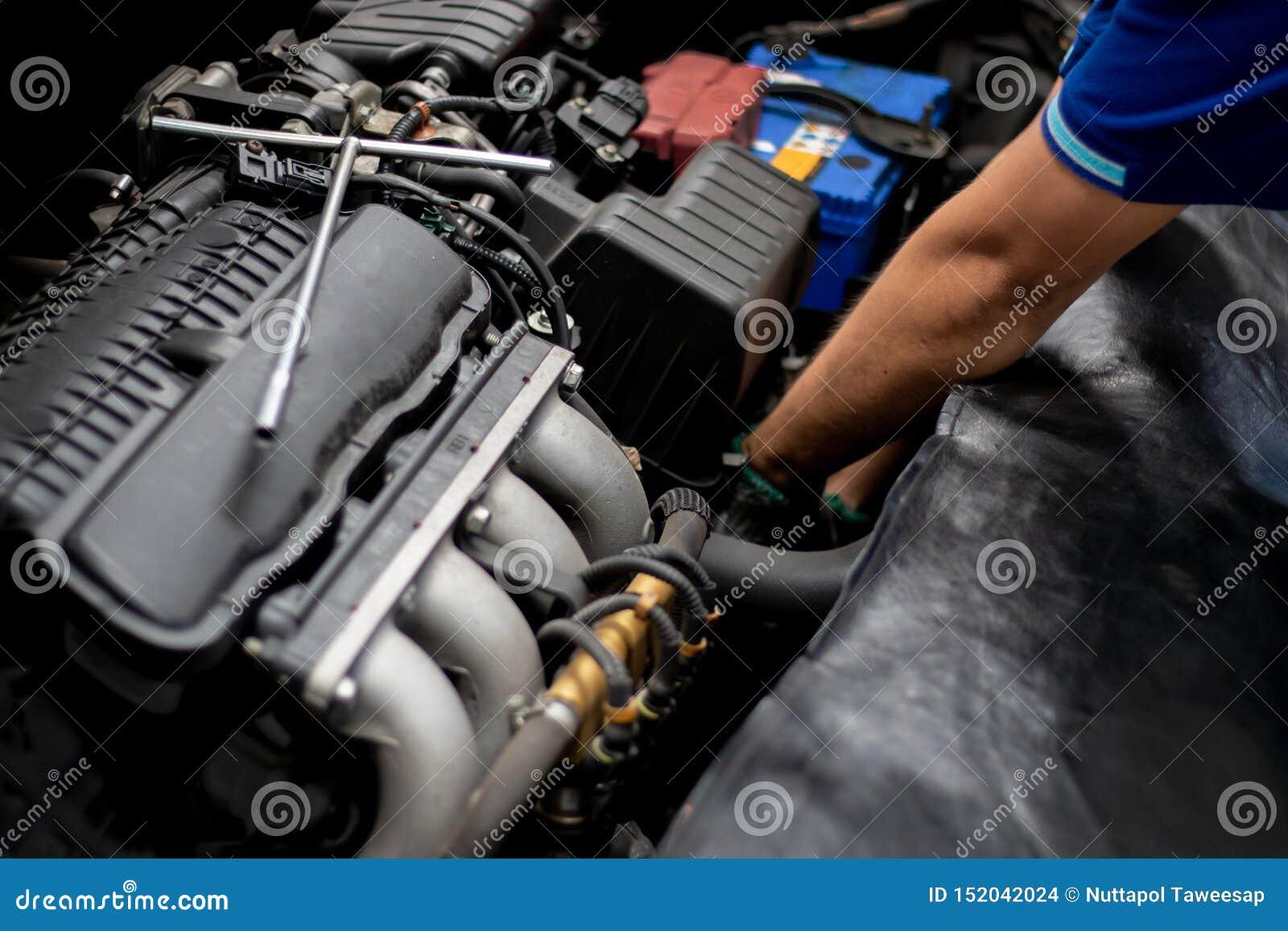 Mekaniker som kontrollerar bilmotorn i den automatiska reparationen