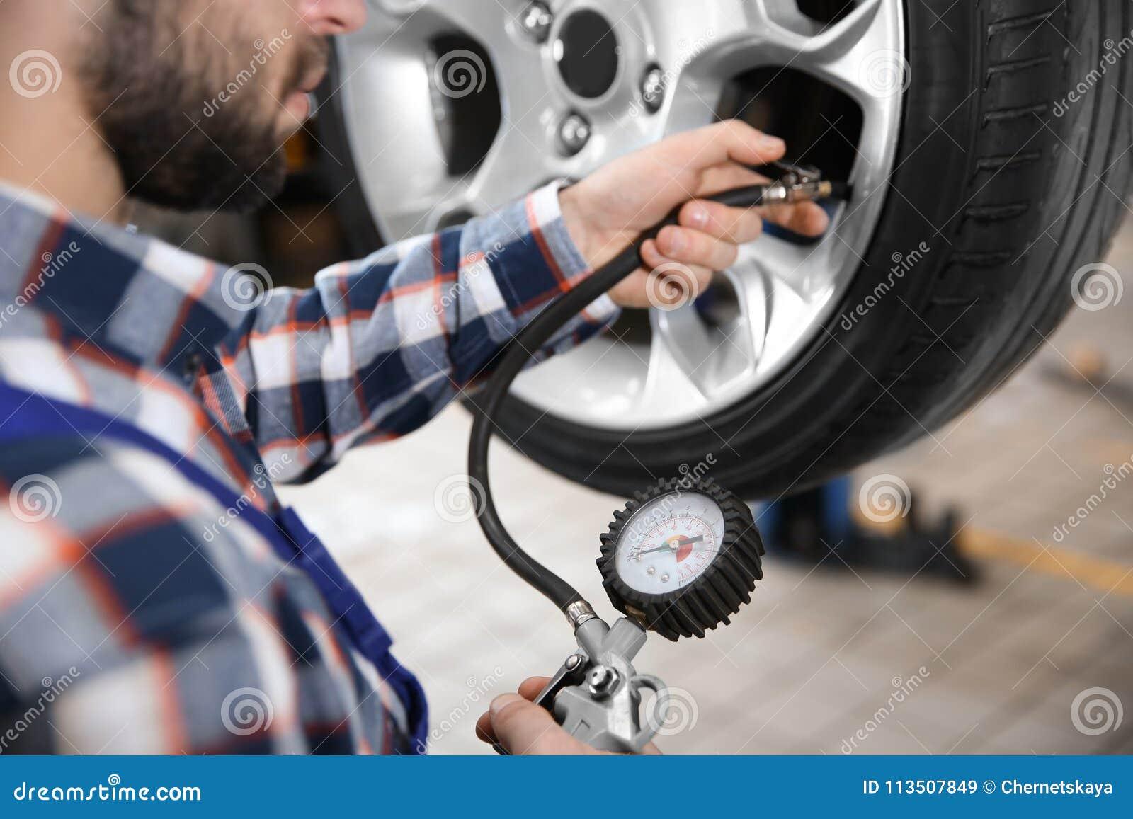 Mekaniker som kontrollerar gummihjultryck i tjänste- mitt