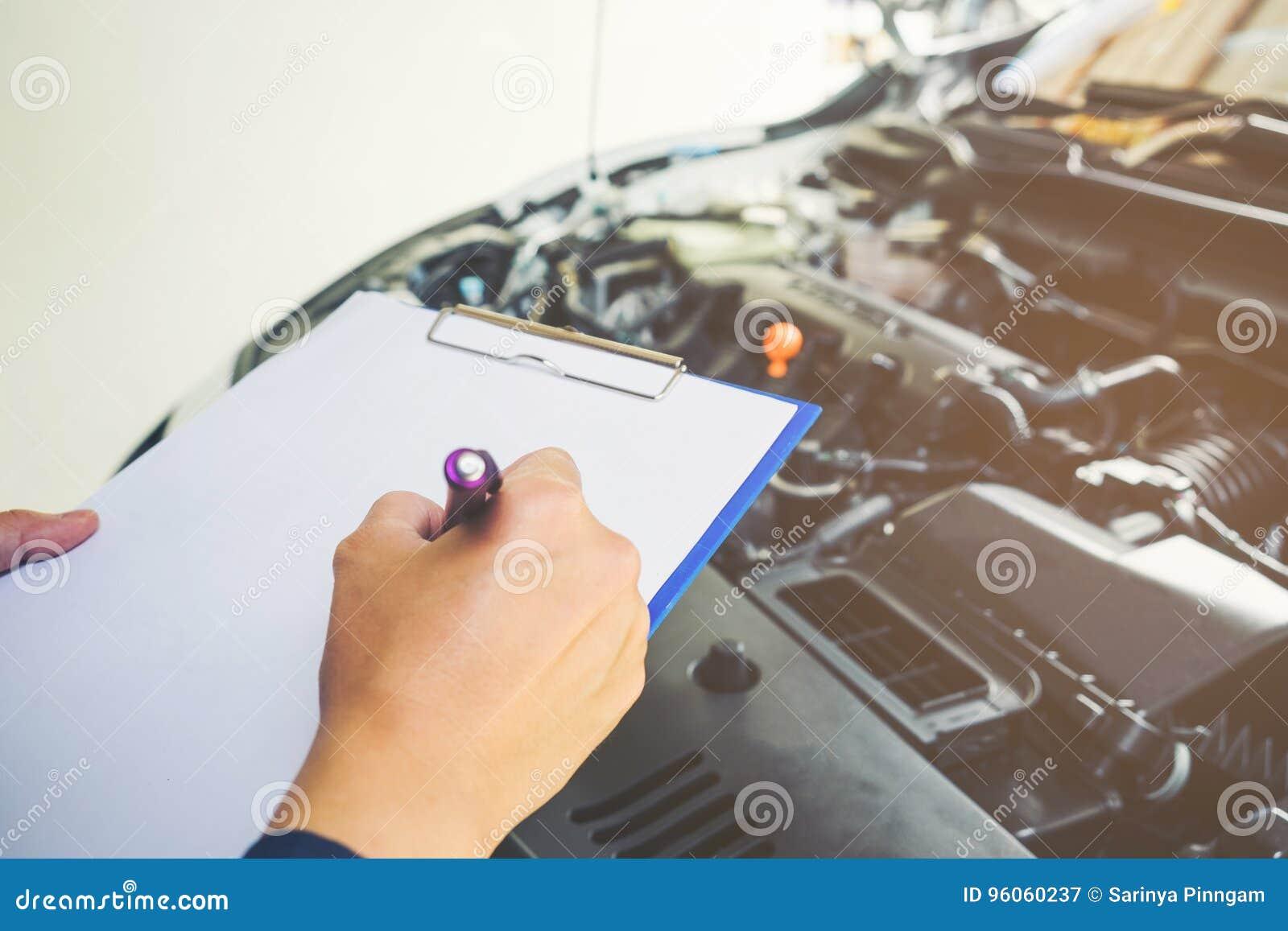 Mekaniker som rymmer en skrivplatta av tjänste- beställning som arbetar i garage
