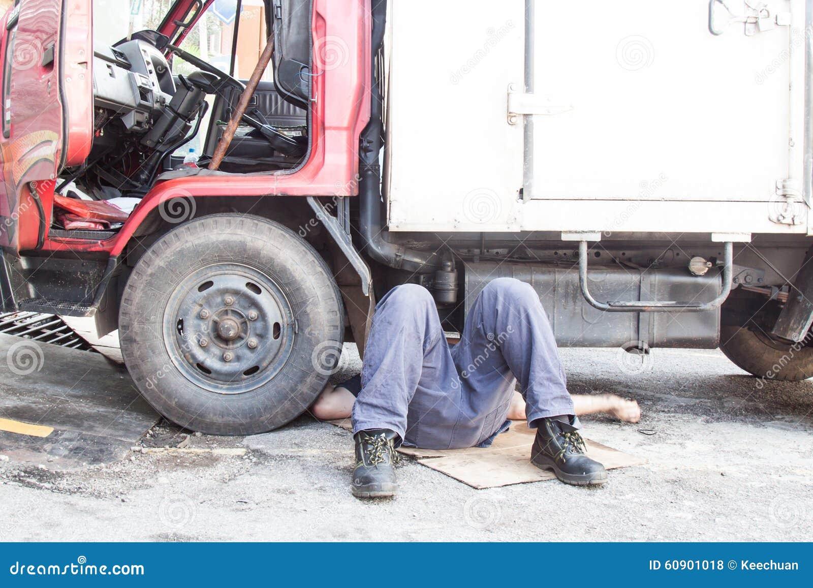 Mekaniker under lastbilen som reparing den smutsiga fetthaltiga oljiga motorn med prob