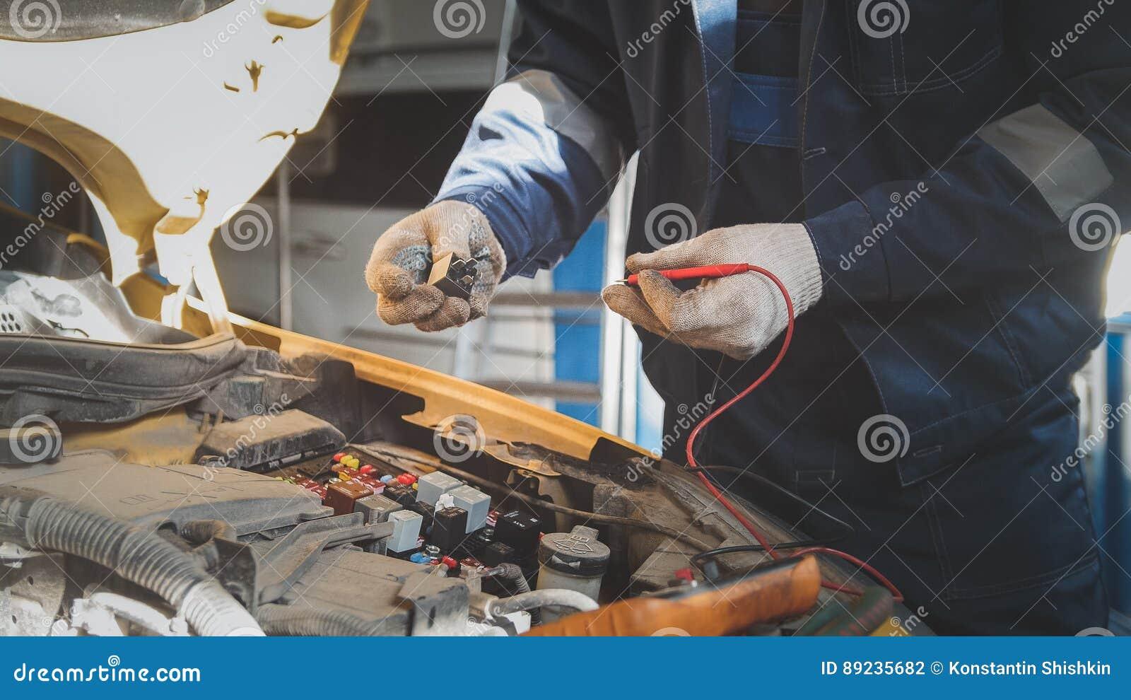 Mekanikern i auto seminarium arbetar med bilelkrafter - elektriskt ledningsnät, voltmeter