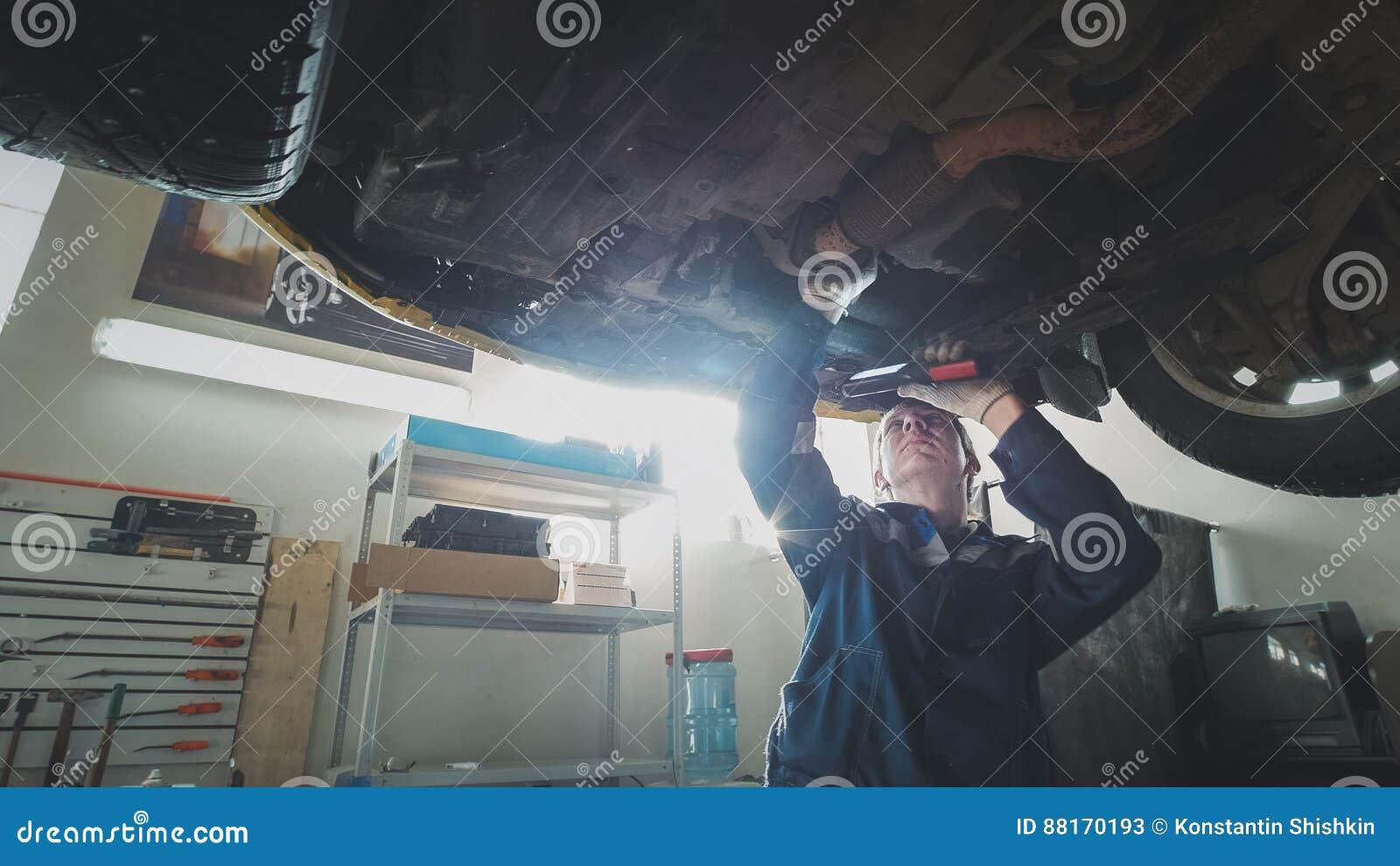 Mekaniskt auto seminarium - en mekaniker kontrollerar upphängningen av bilen, bred vinkel
