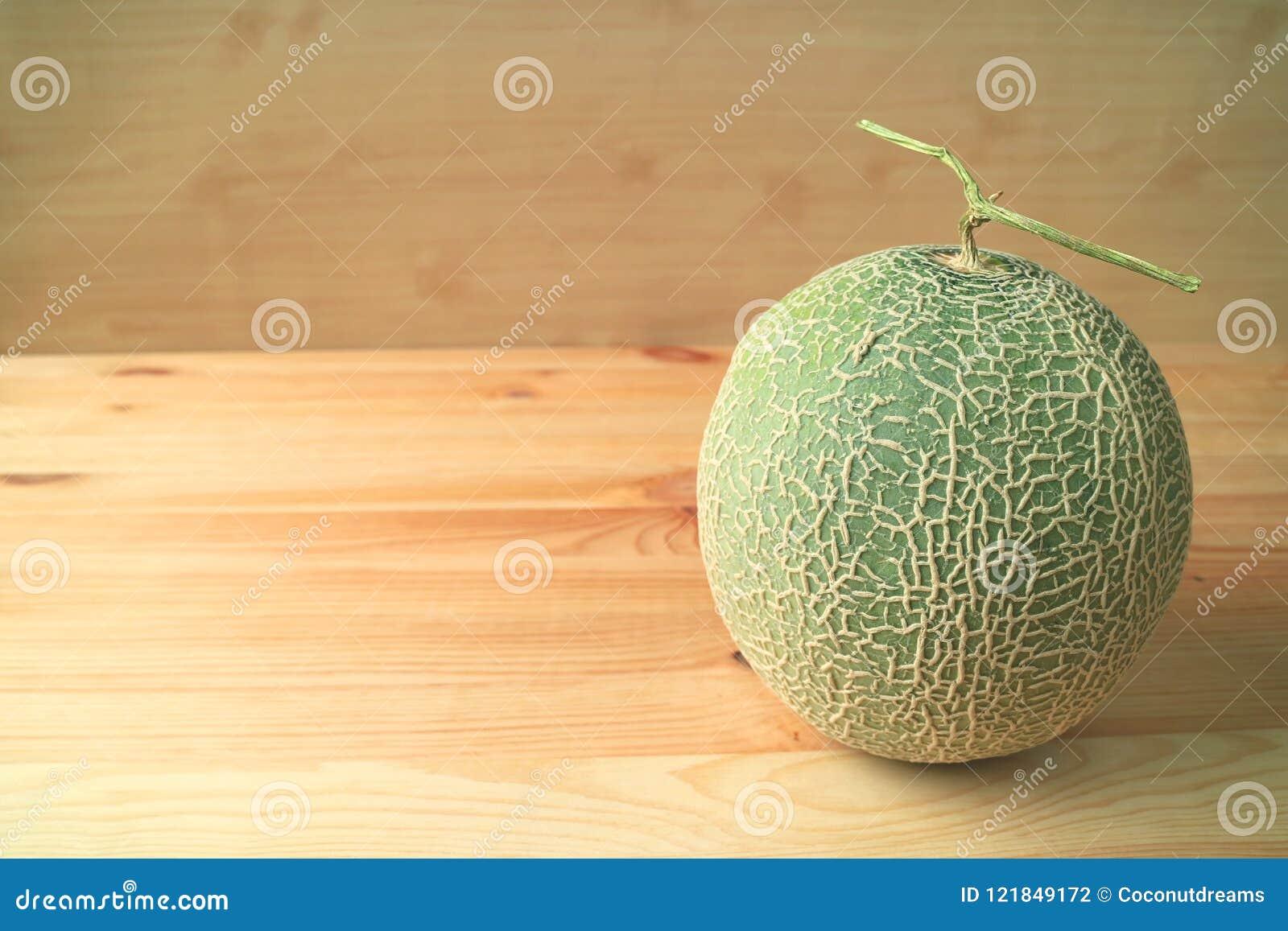 Melón maduro fresco del cantalupo o fruta entera del melón con el tronco aislado en la tabla de madera