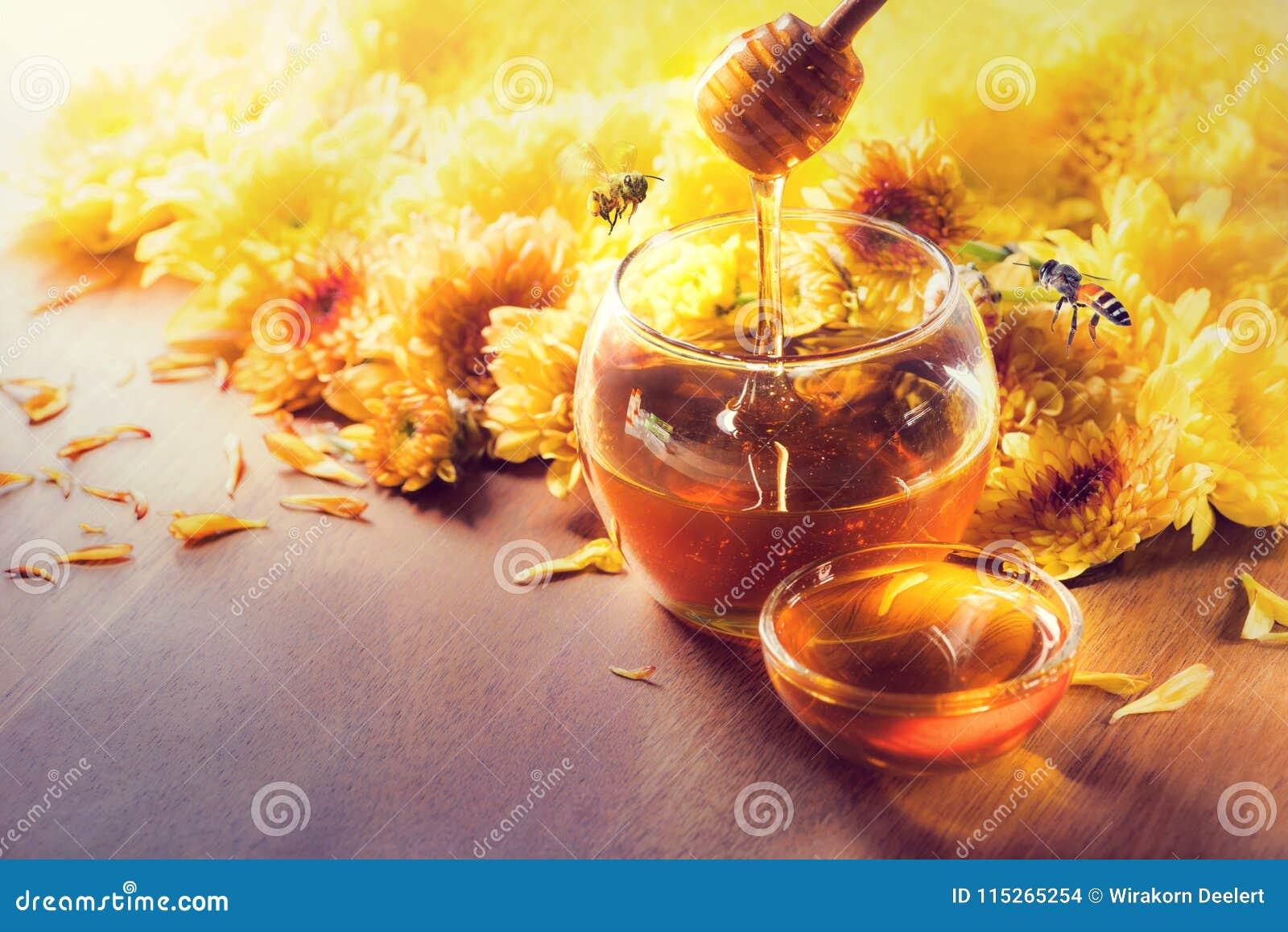 Mel no frasco de vidro com voo e flores da abelha em um assoalho de madeira