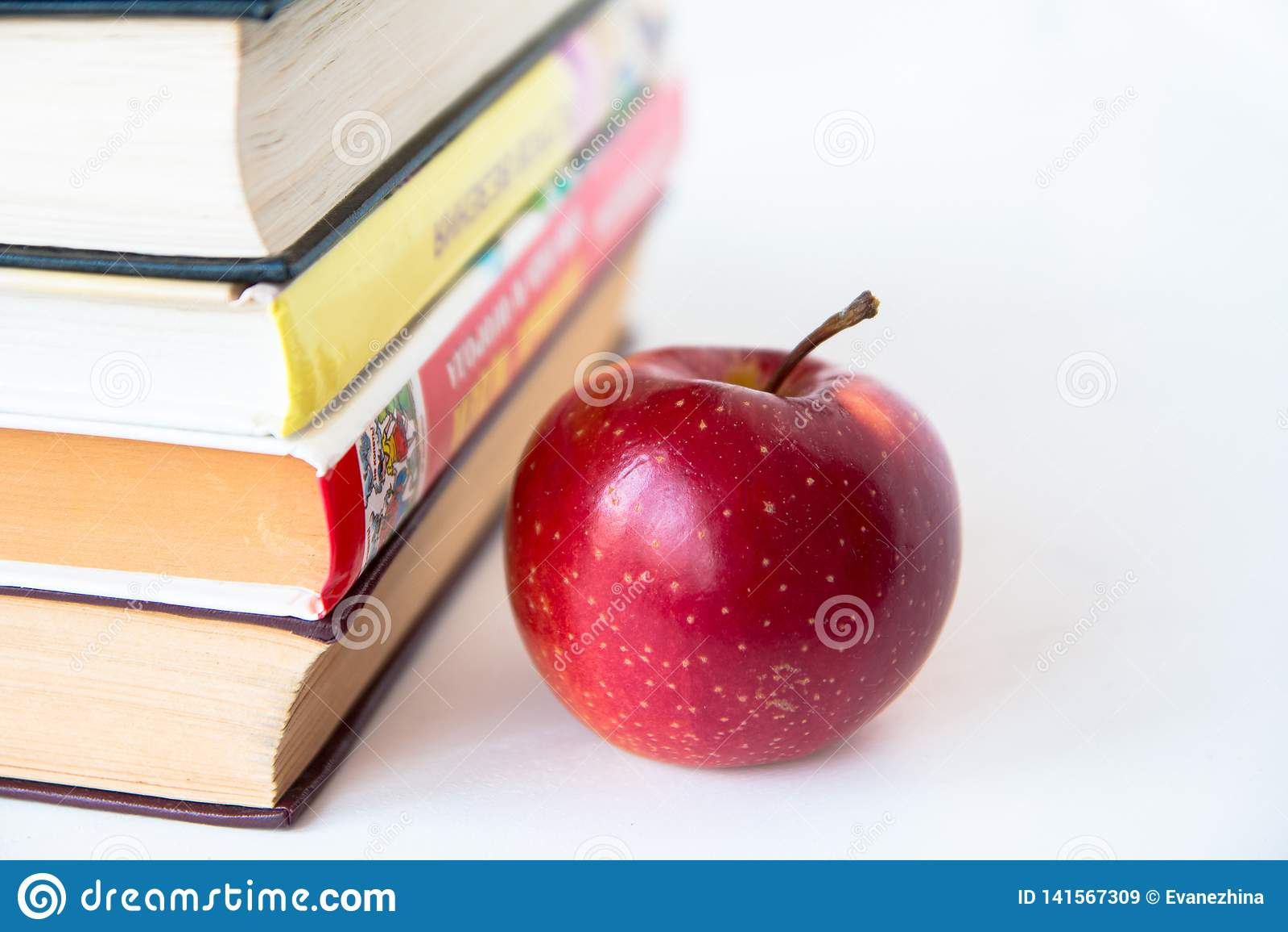 Mela succosa matura rossa vicino ai libri