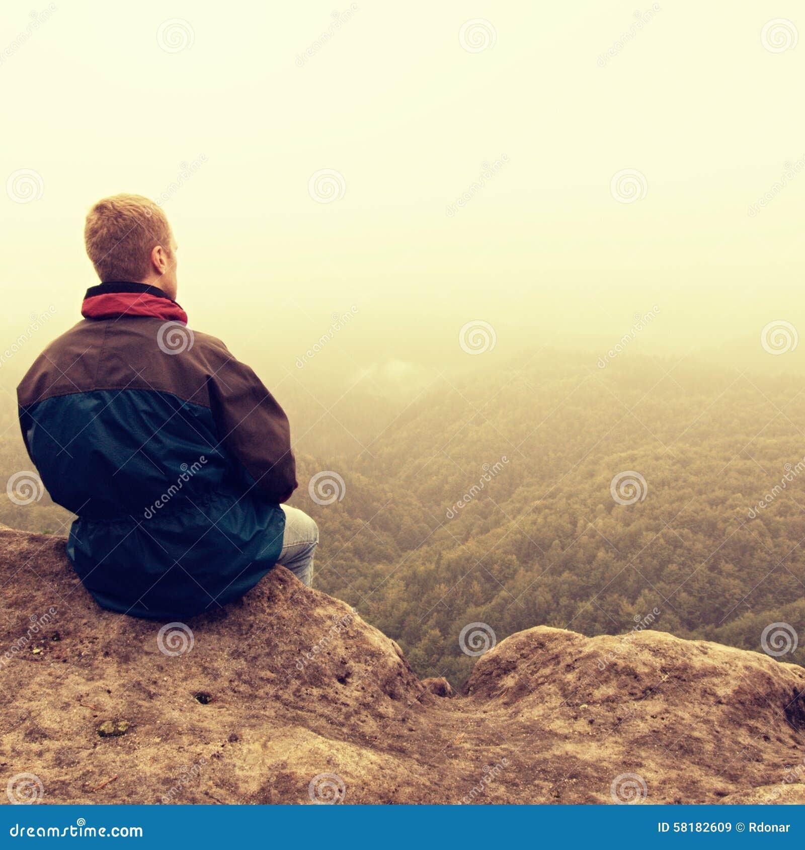 Melancholiczny i smutny dzień Mężczyzna przy enge skała nad głęboki vally Turysta na szczycie piaskowiec skały dopatrywanie zapar