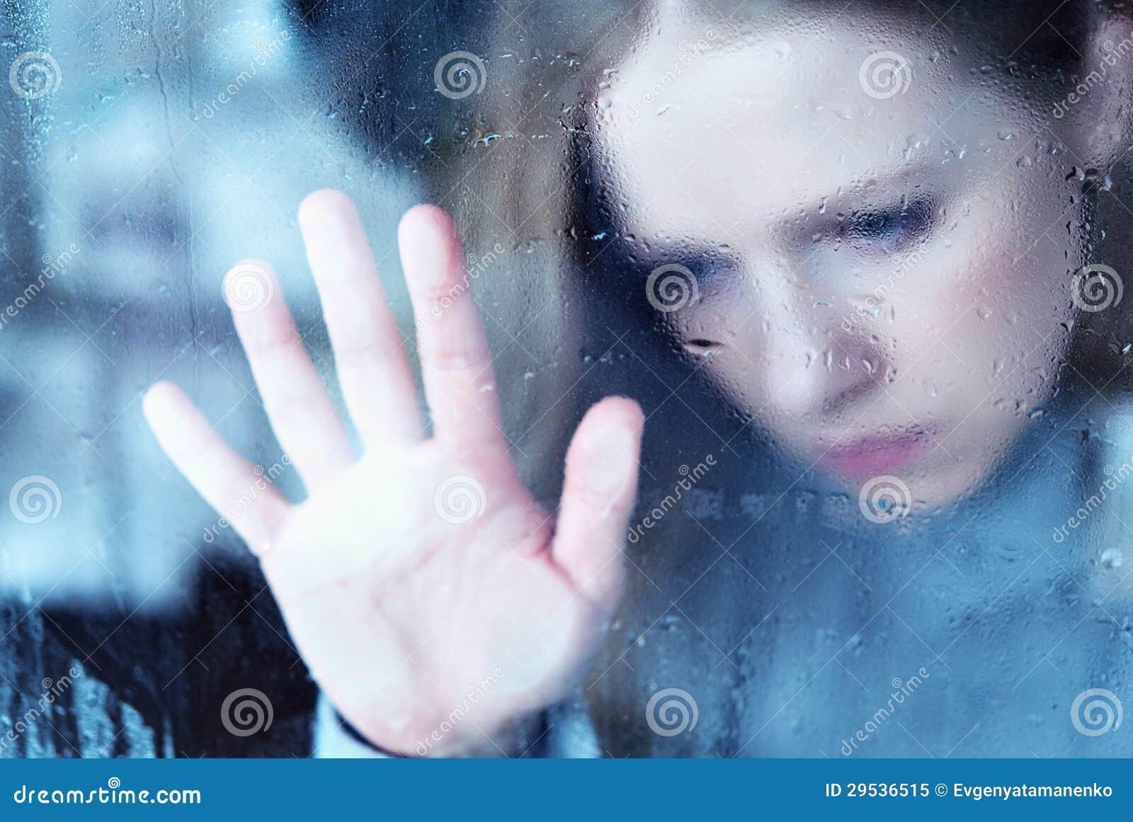 Melancholisch en droevig meisje bij het venster in de regen