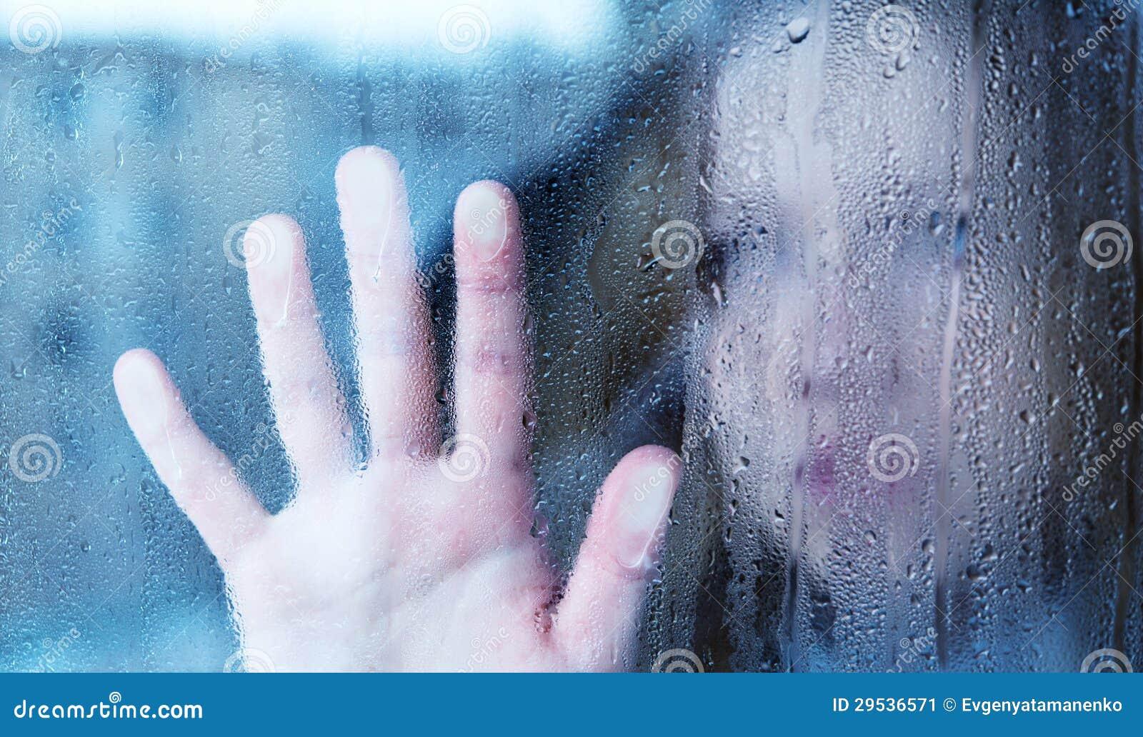 Melancholische en droevige jonge vrouw bij het venster in de regen