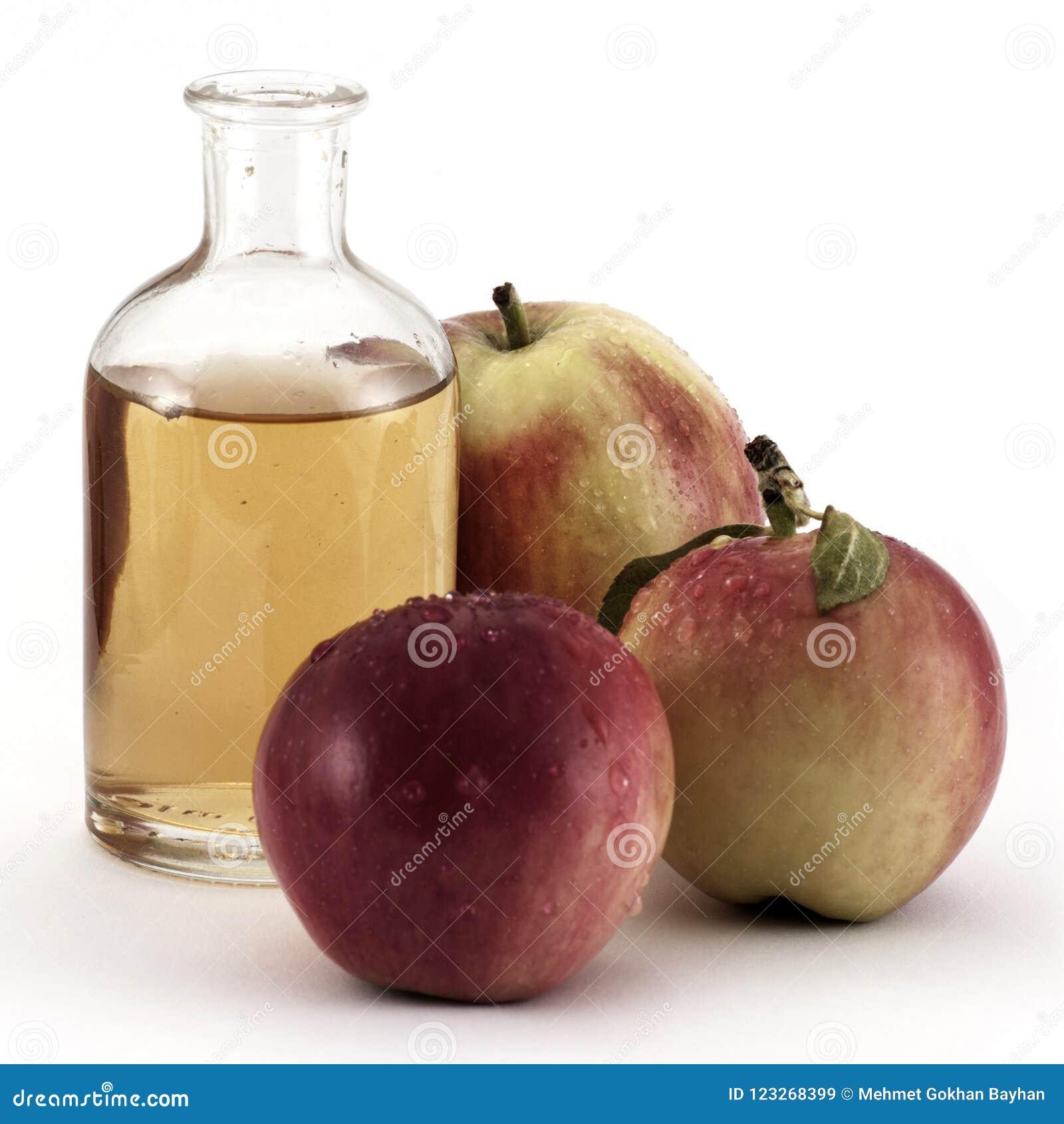 Mele ed aceto rossi della mela in bottiglia di vetro su bianco