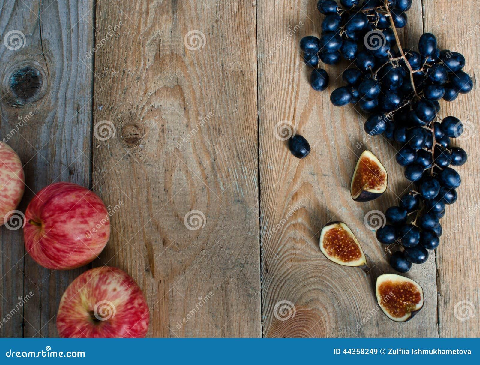 Mele, uva e fichi su fondo di legno