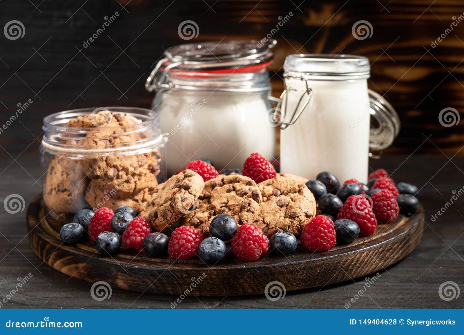 Melk, koekjes, bloemontvangers en bosdievruchten op rond gemaakte houten schotel wordt geplaatst