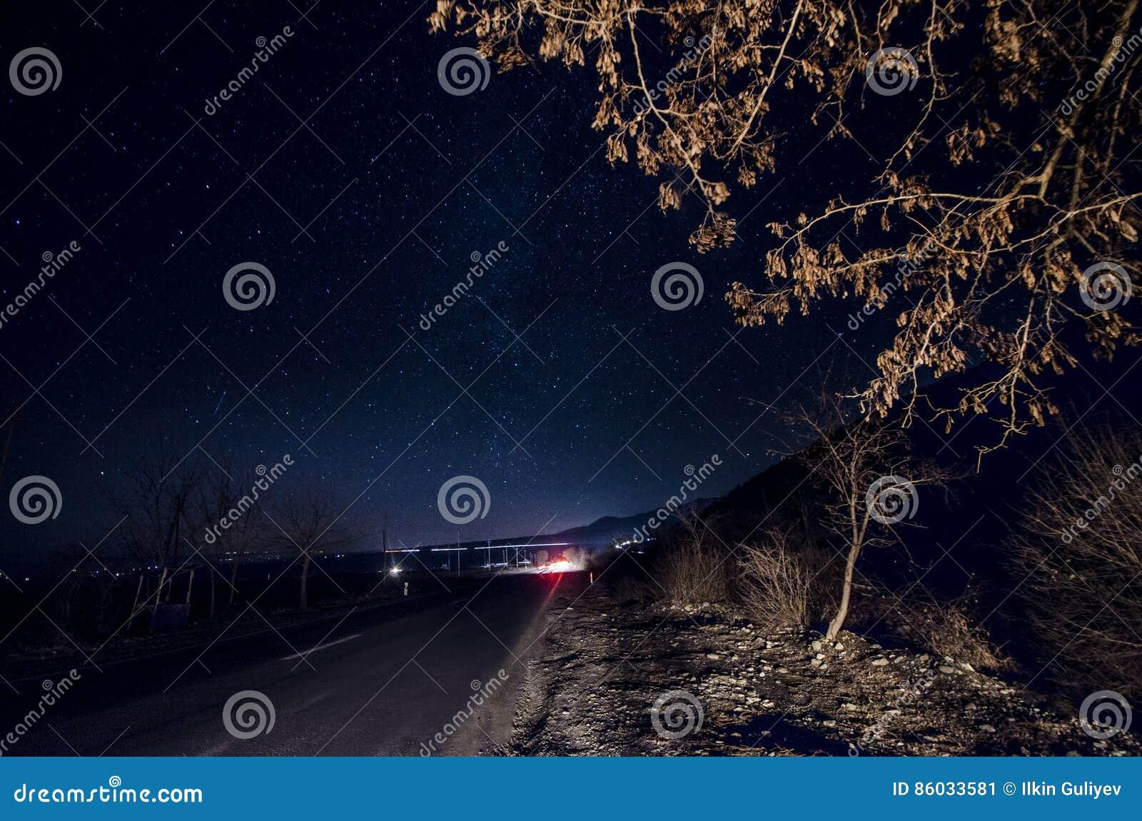 Melkweg boven weg en boom dichte omhooggaand met autolichten op brenches Nachtweg met sterren op hemel, Sheki, Azerbeidzjan