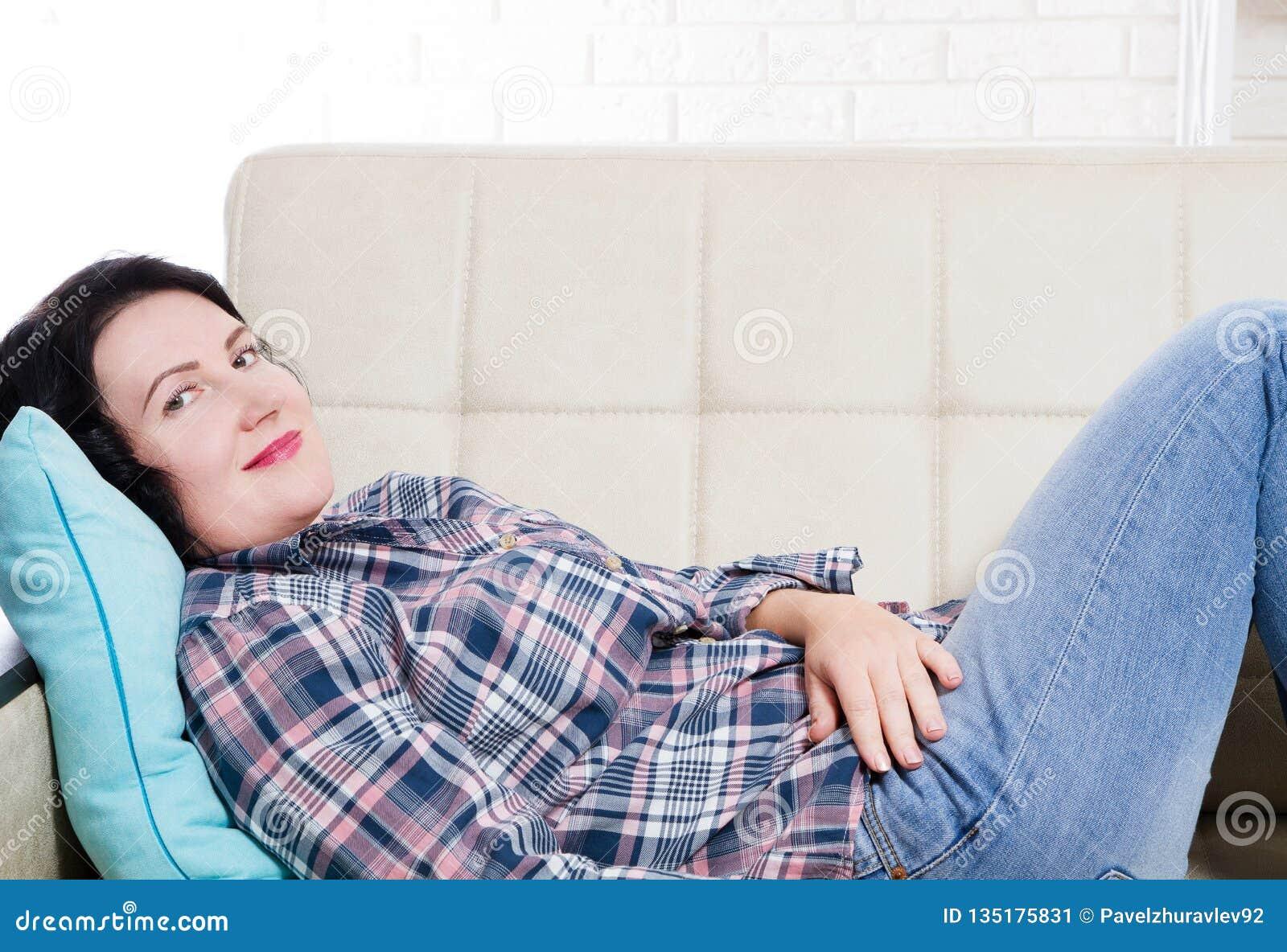Mellersta ålder som ler kvinnalögner på soffan och att se Ung brunettkvinna som hemma tänker i en fritid