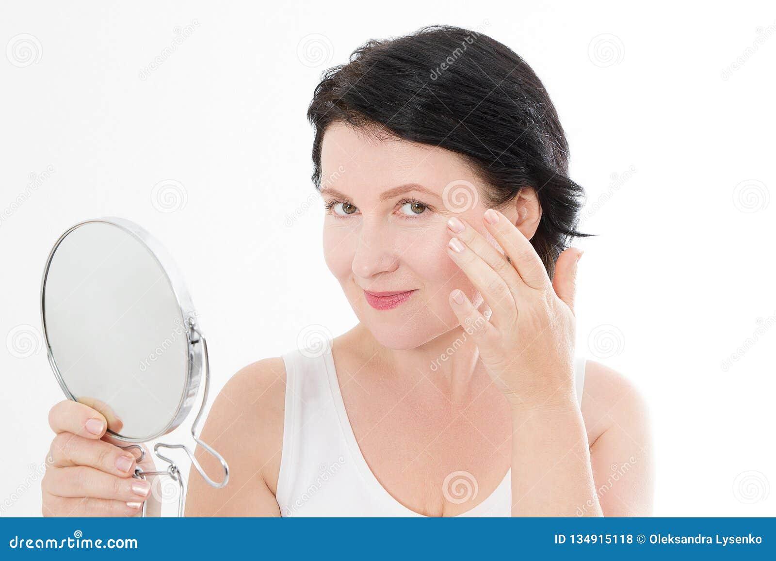 Mellersta ålderkvinna för skönhet med spegeln Isolerat på vit Spa och anti-åldras begrepp som isoleras på vit bakgrund mature öve