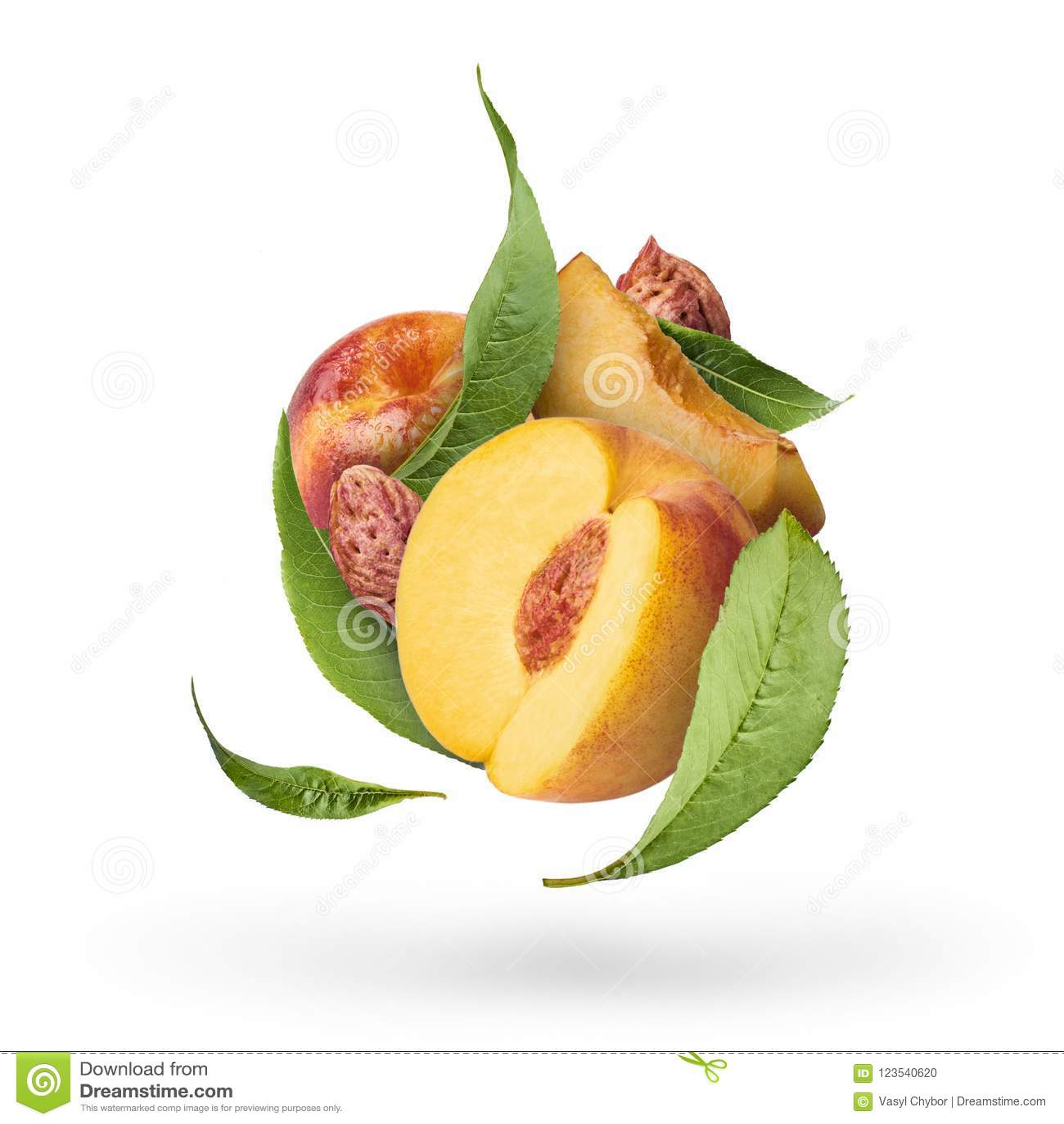 Melocotón maduro fresco que vuela con las hojas del verde aisladas