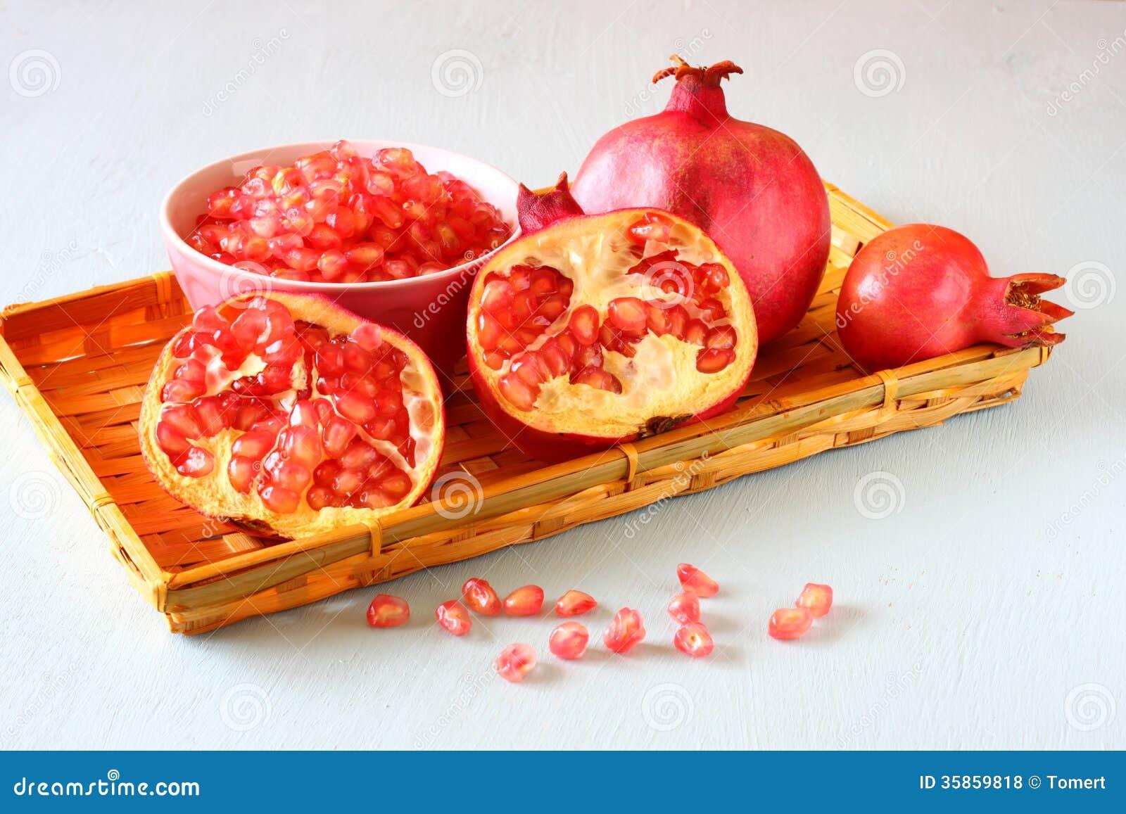 Melograno sulla tavola di legno e seme fresco del pomegrante in ciotola
