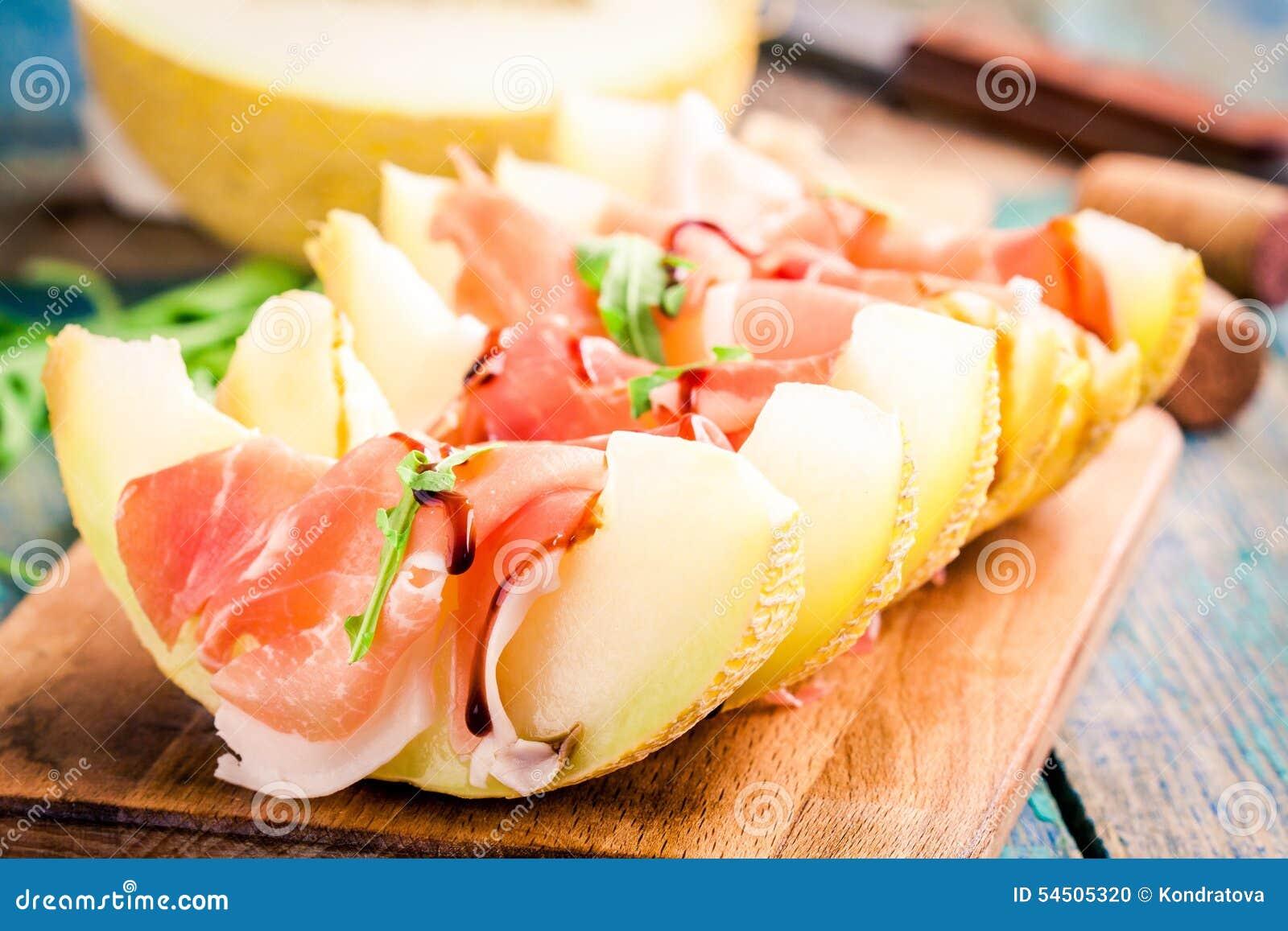 Melon avec les tranches minces de feuilles de prosciutto et d arugula