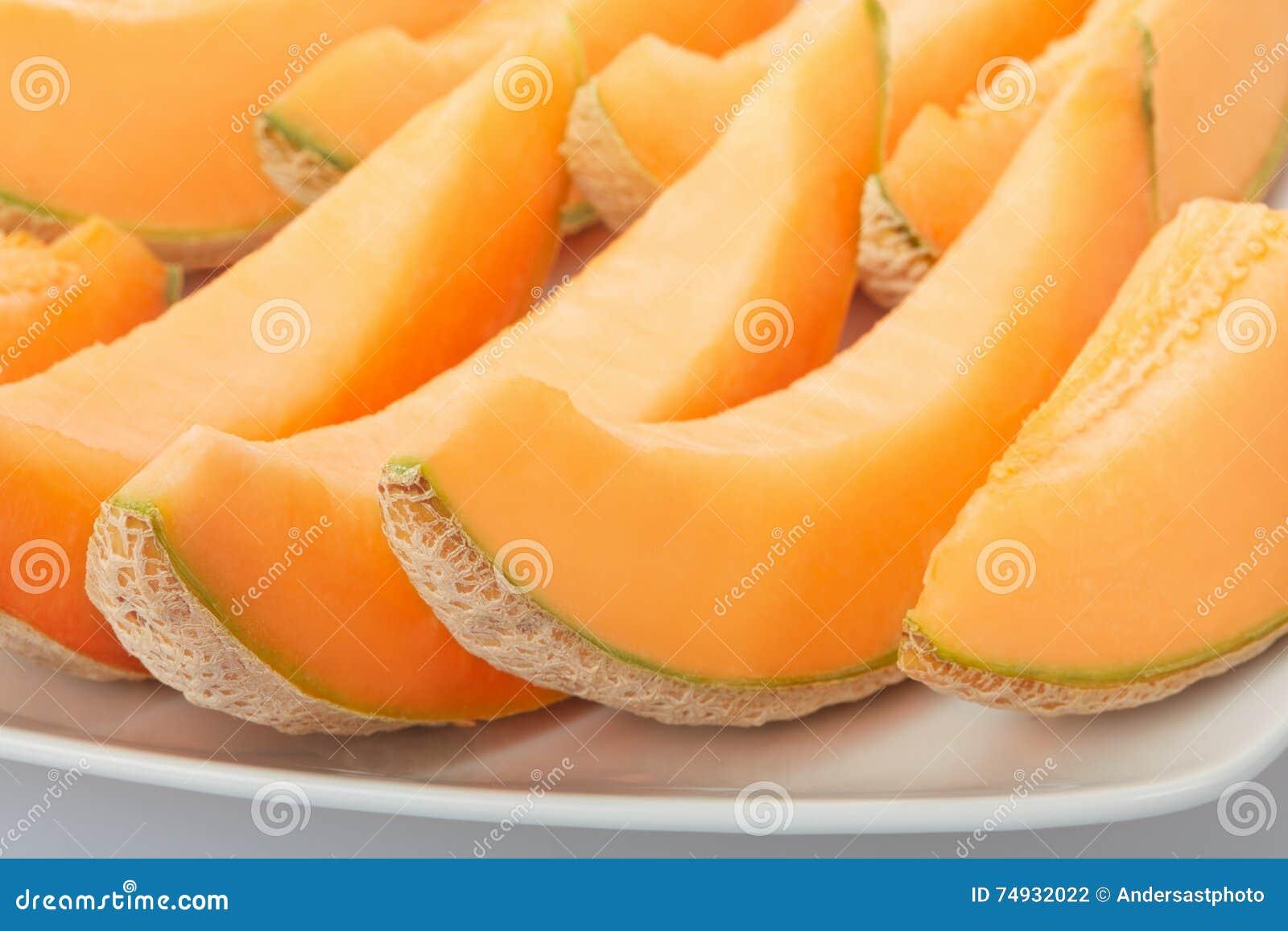 Melon de cantaloup, tranches oranges sur le plat