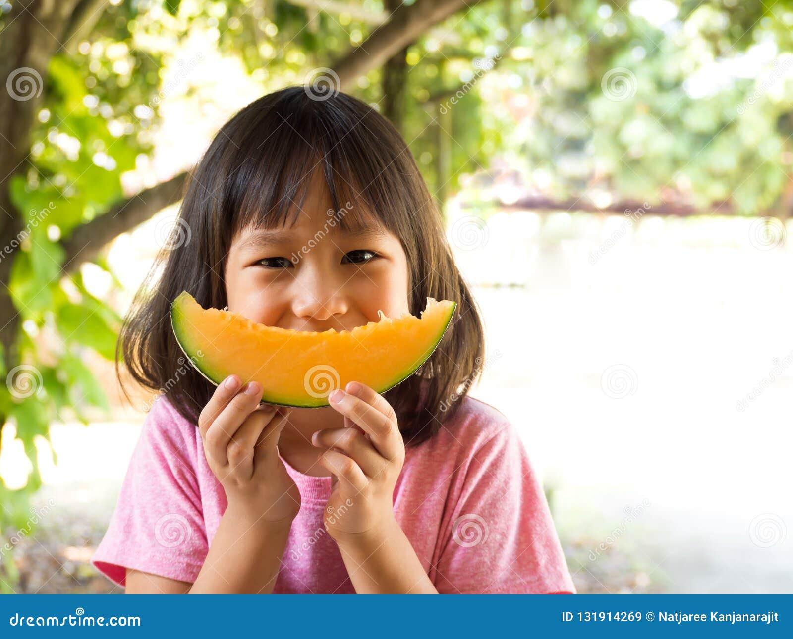 Melone arancio della ragazza della fetta asiatica della tenuta sulle mani Assomigli al melone