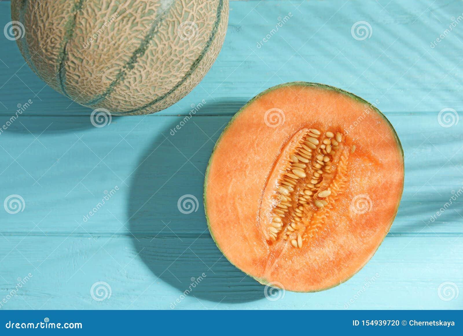 Melones maduros sabrosos del cantalupo y sombra de hoja de palma en la tabla de madera azul clara