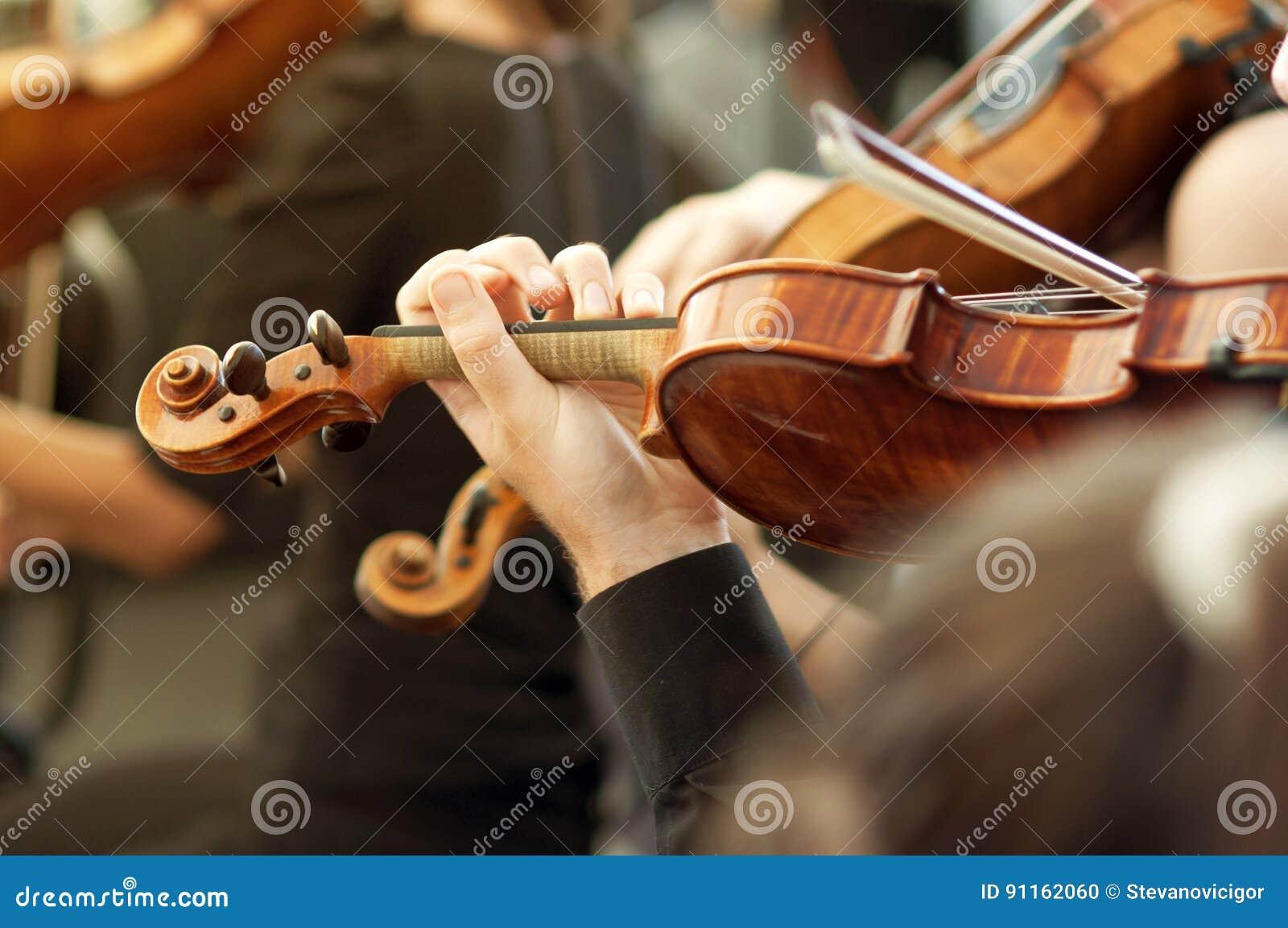Membro da orquestra da música clássica que joga o violino em um concerto