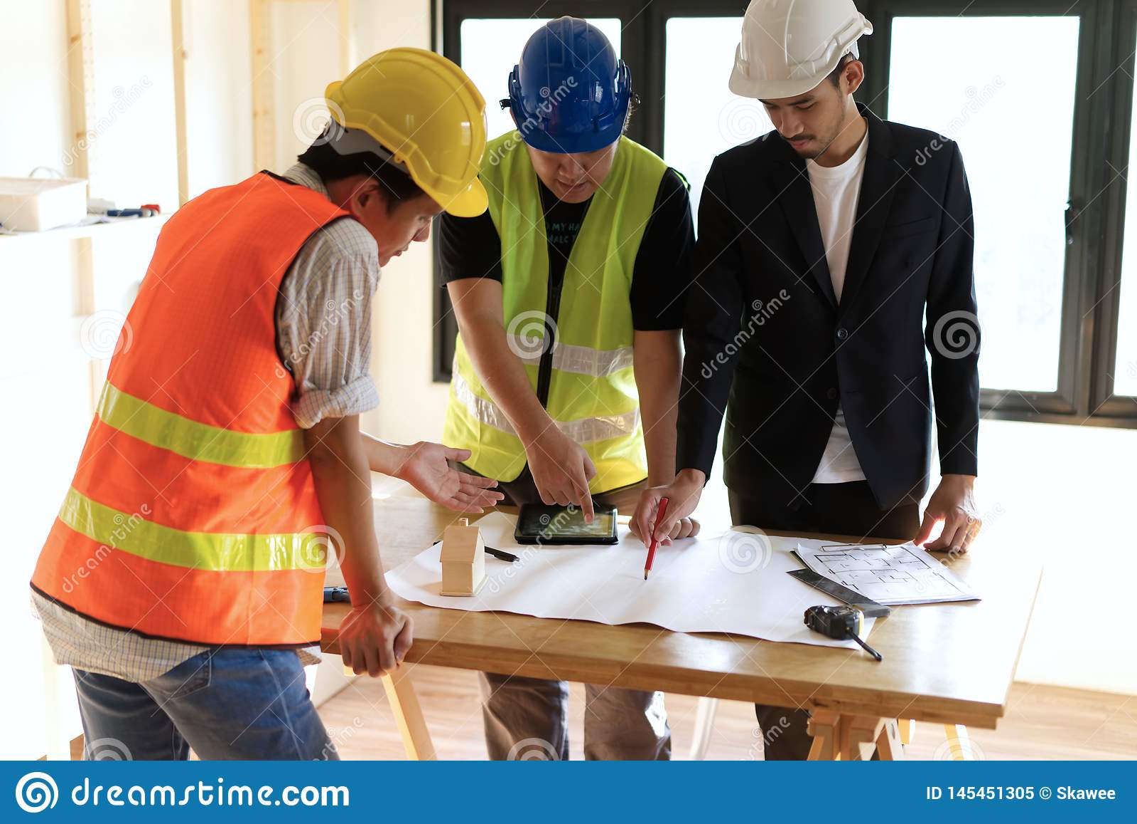 Membros da construção de casas que recolhem na tabela de funcionamento que tem alguma discussão para o planeamento de projeto
