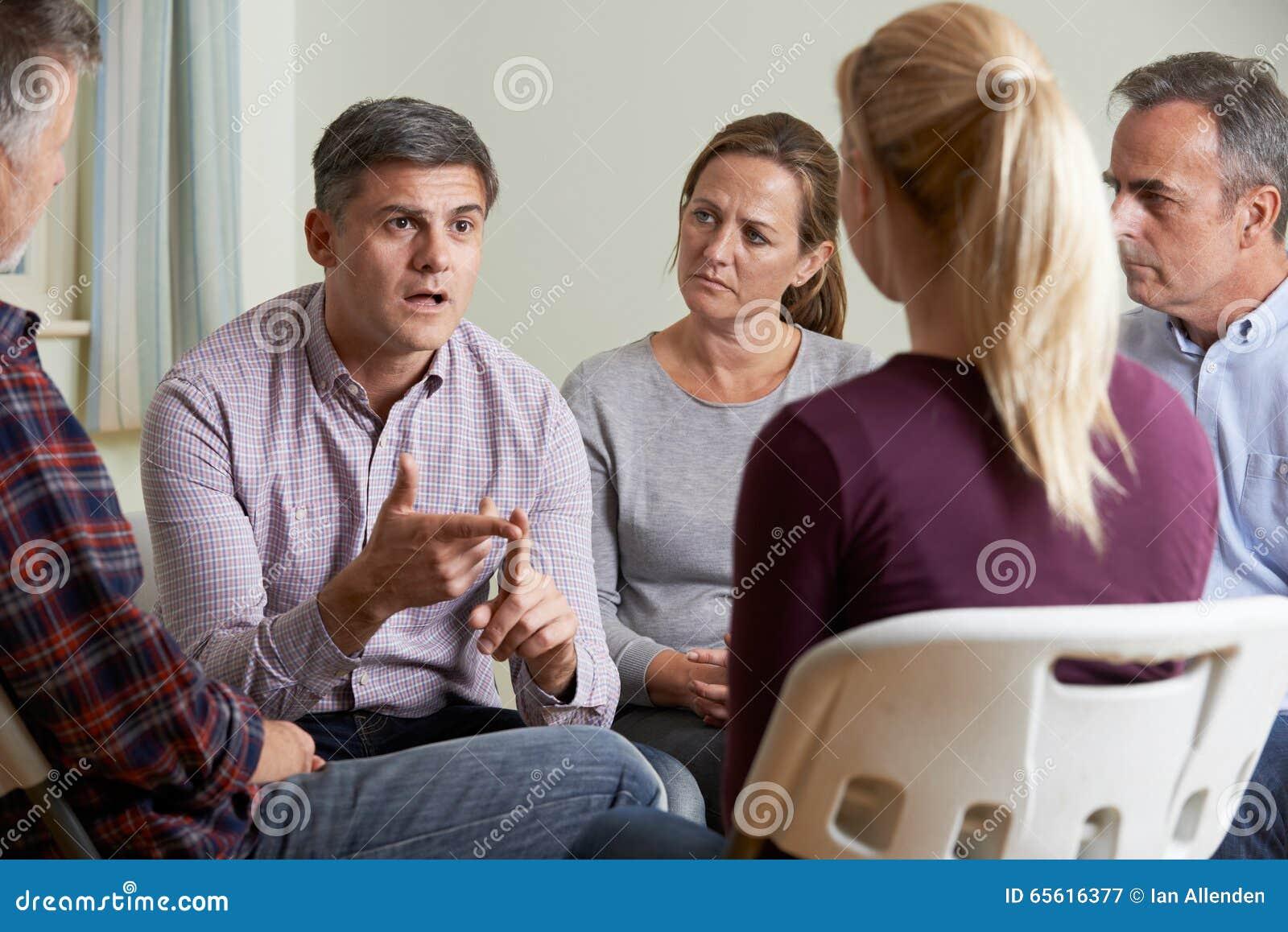 Membros do grupo de apoio que sentam-se nas cadeiras que têm a reunião