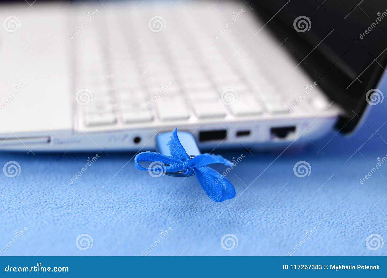 Memoria USB azul brillante con un arco azul está conectada con un ordenador portátil blanco, que miente en una manta de la luz su
