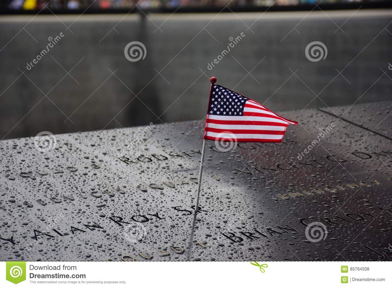 Memorial at Ground Zero Manhattan for September 11 Terrorist Attack with an American Flag Standing near the Names of Victims Engra