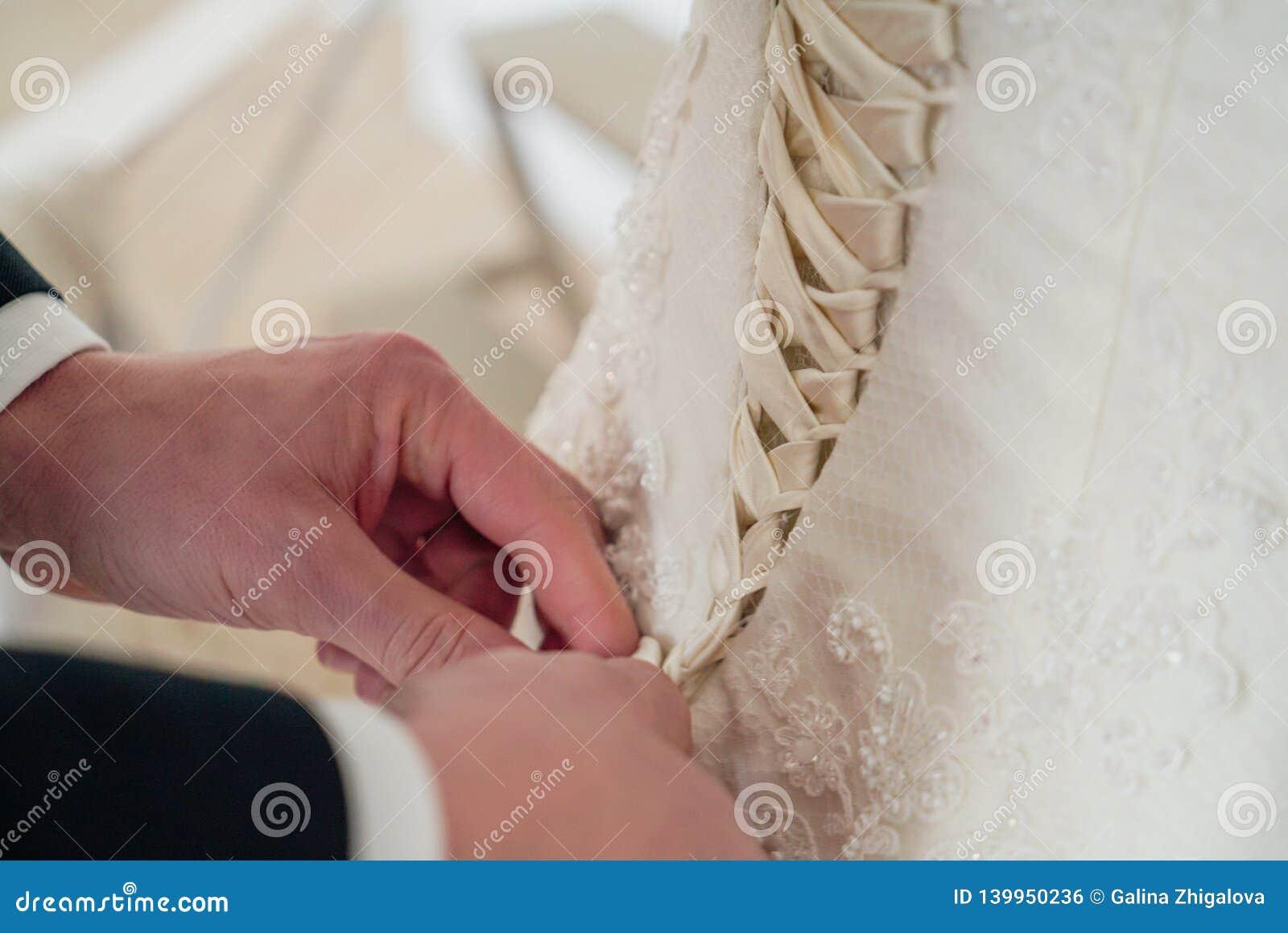Men& x27; as mãos de s atam acima o espartilho no bride& x27; vestido de s, fim acima