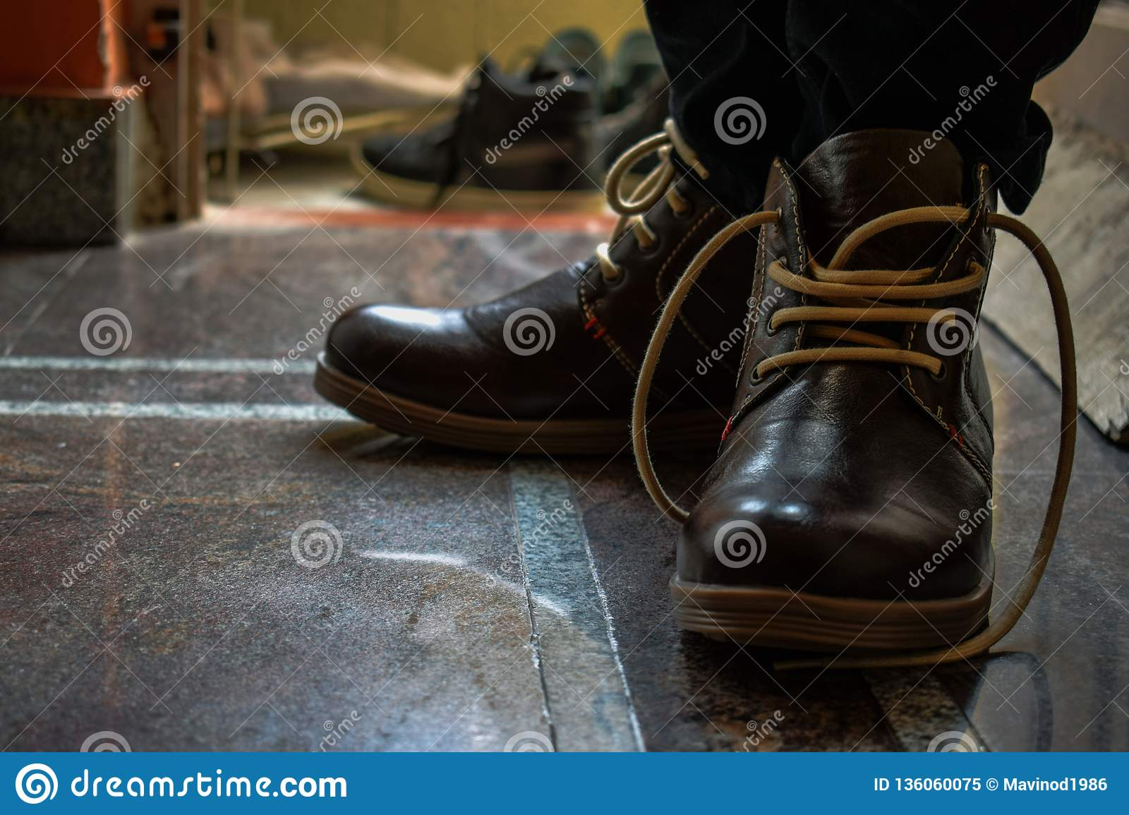 Men brown boots with brown laces posing for the perfect picture