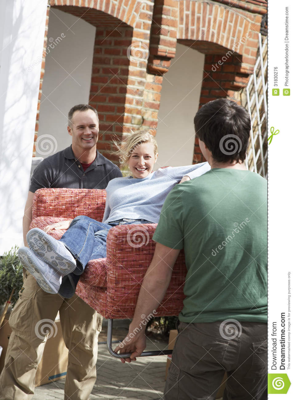 Men Carrying Woman On Sofa Outdoors Stock Photo Image