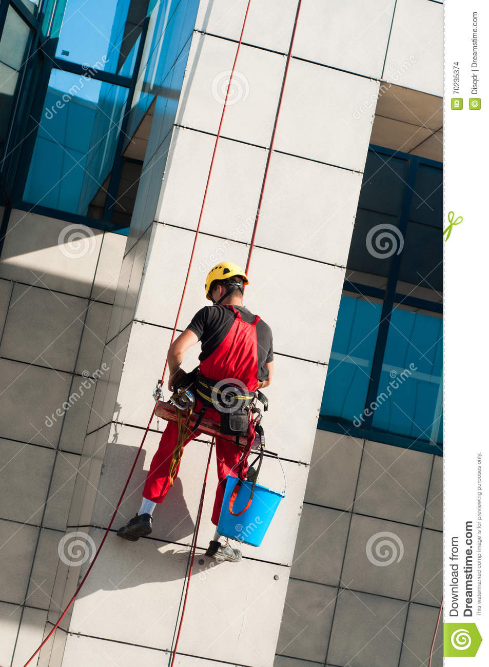 Man cleaning office building hanging on ropes