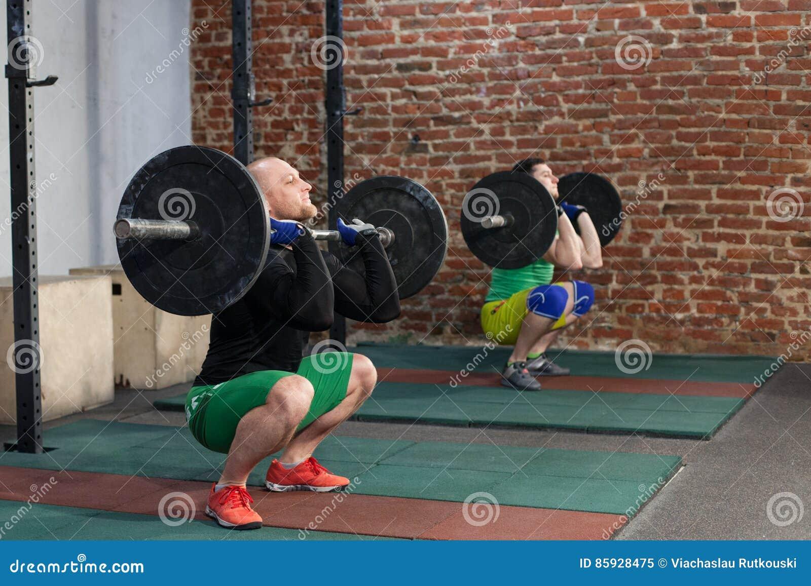 Men doing squat with barbells