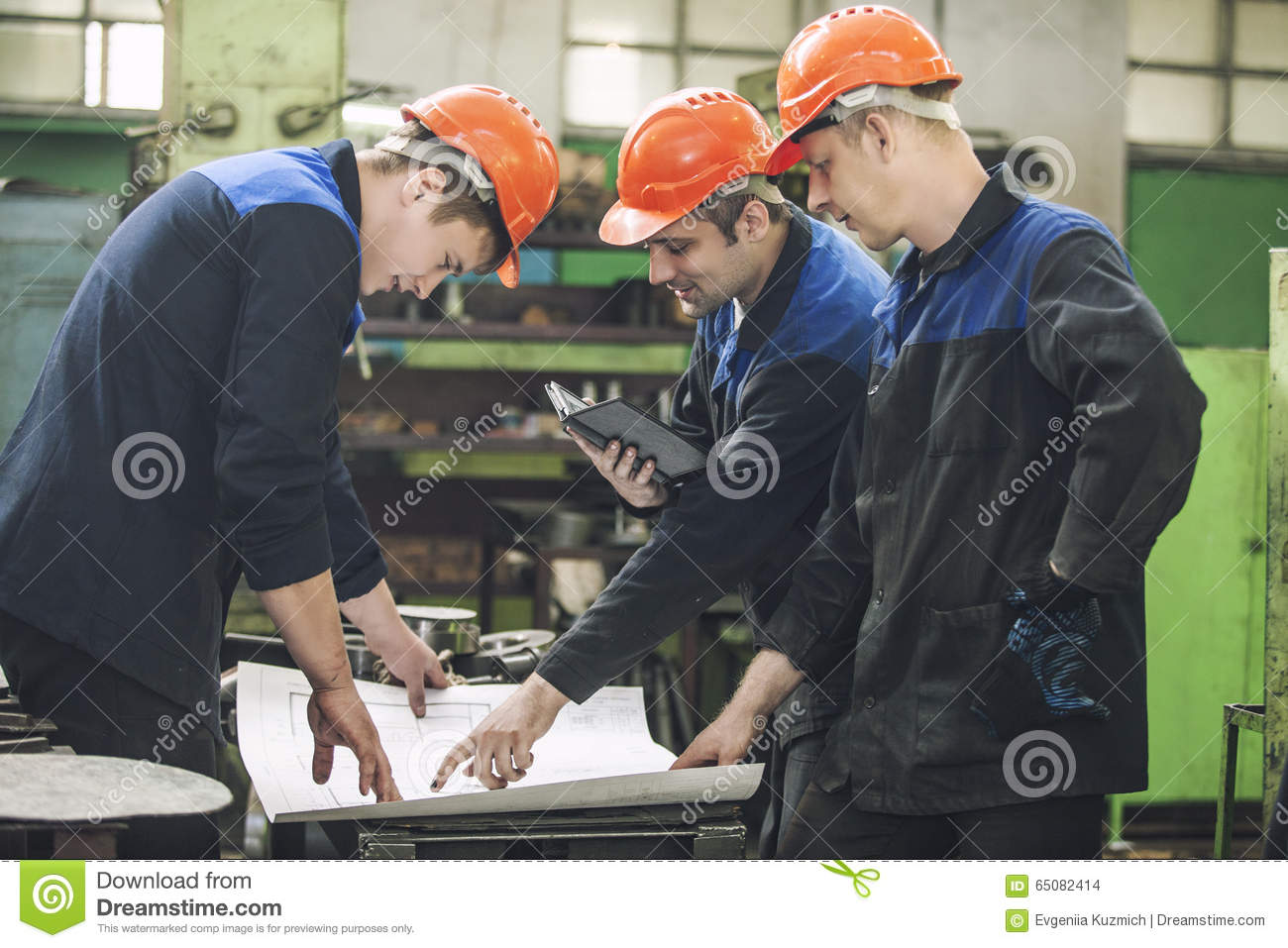 Men with drawings working in an old factory to install the equip