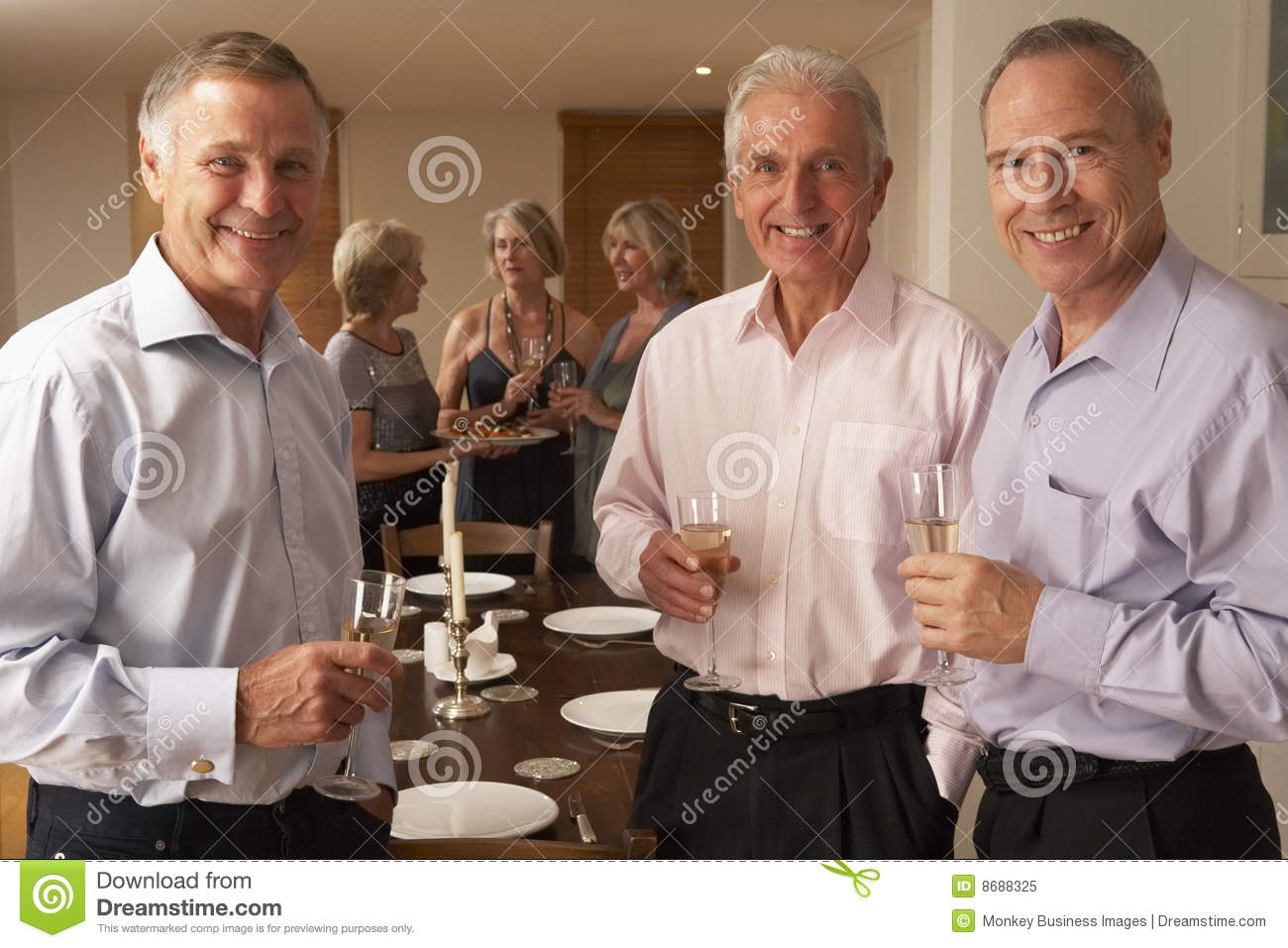Men Enjoying Champagne At A Dinner Party Royalty Free