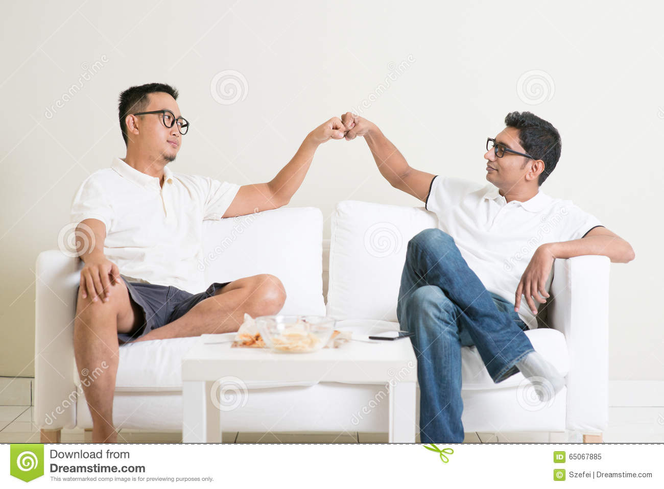 Fist bump stock photos royalty free images men fist bump man sitting on sofa and giving fist bump to friend at home m4hsunfo