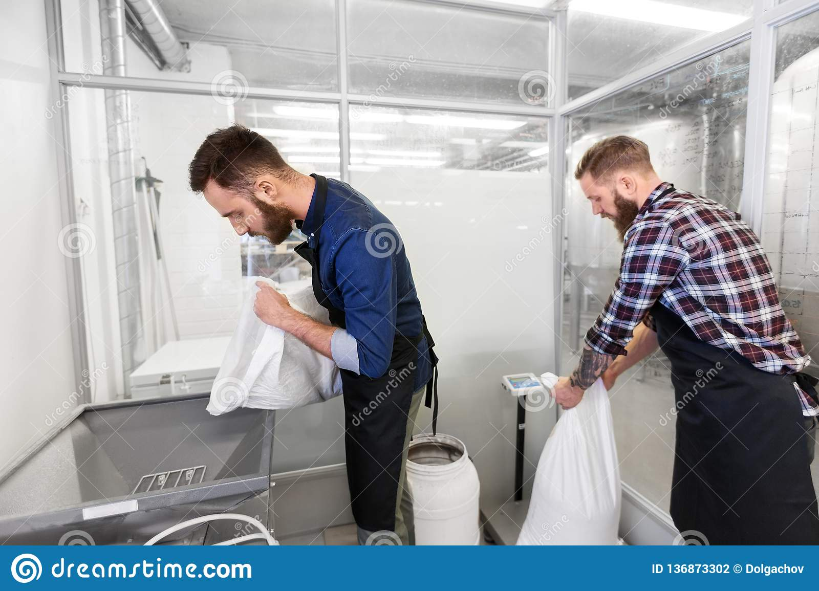 Men With Malt Bags And Mill At Craft Beer Brewery Stock