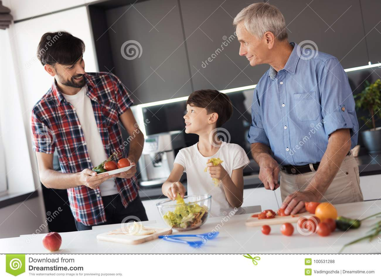 The boy is preparing a salad for dinner on Thanksgiving Day with his father and grandfather