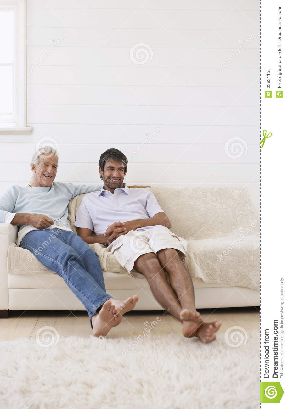 Men Relaxing On Sofa At Home Royalty Free Stock Image