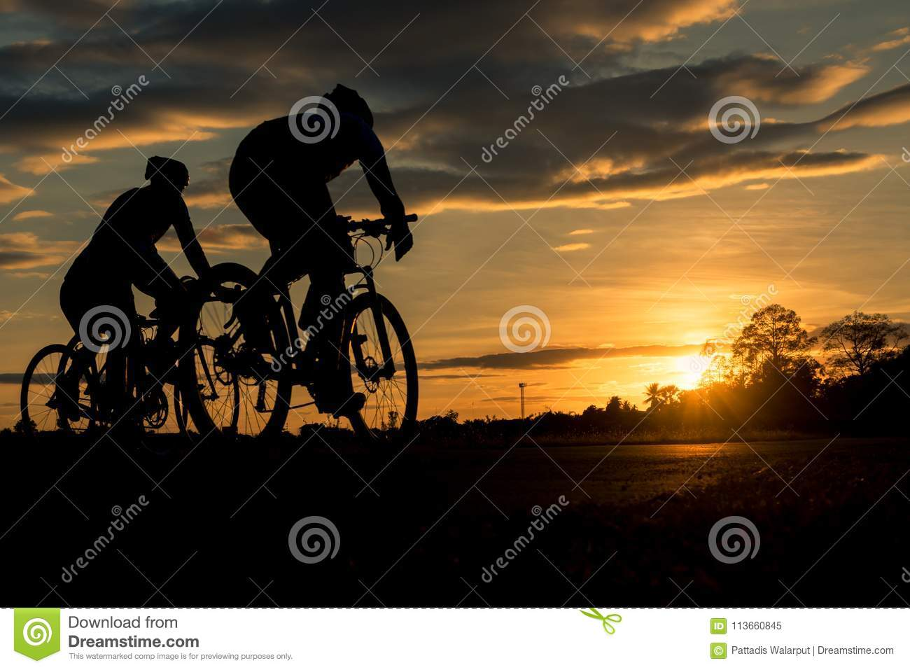 The men ride bikes at sunset with orange-blue sky background.