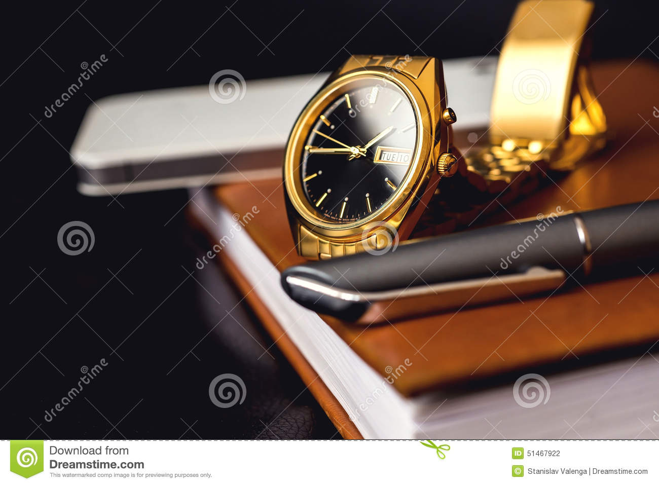 Men s accessory, golden watch, pen and mobile phone on the leather diary.