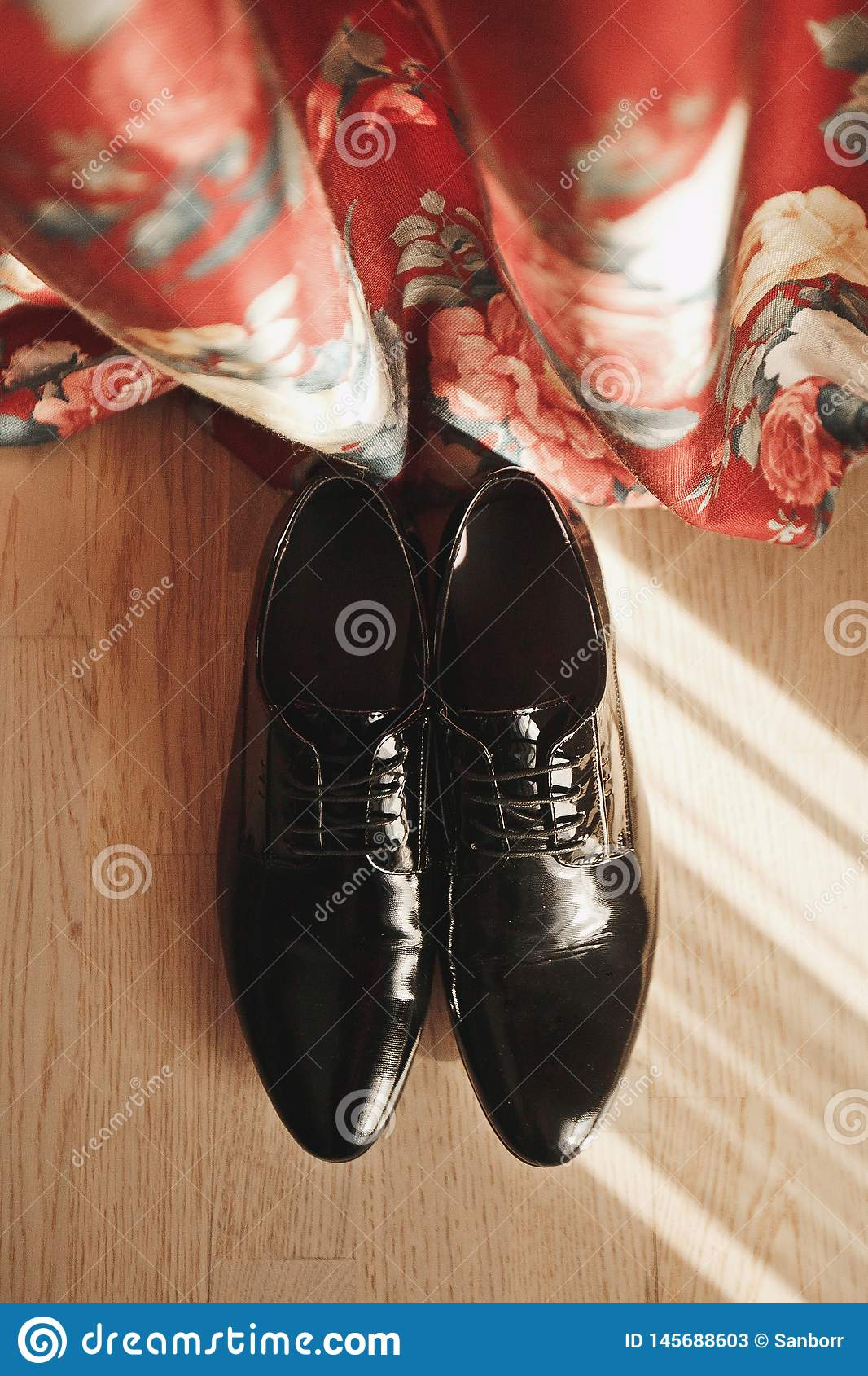Men`s black leather elegant business shoes on a light floor, on a background of red bright curtains, close-up. New luxury modern